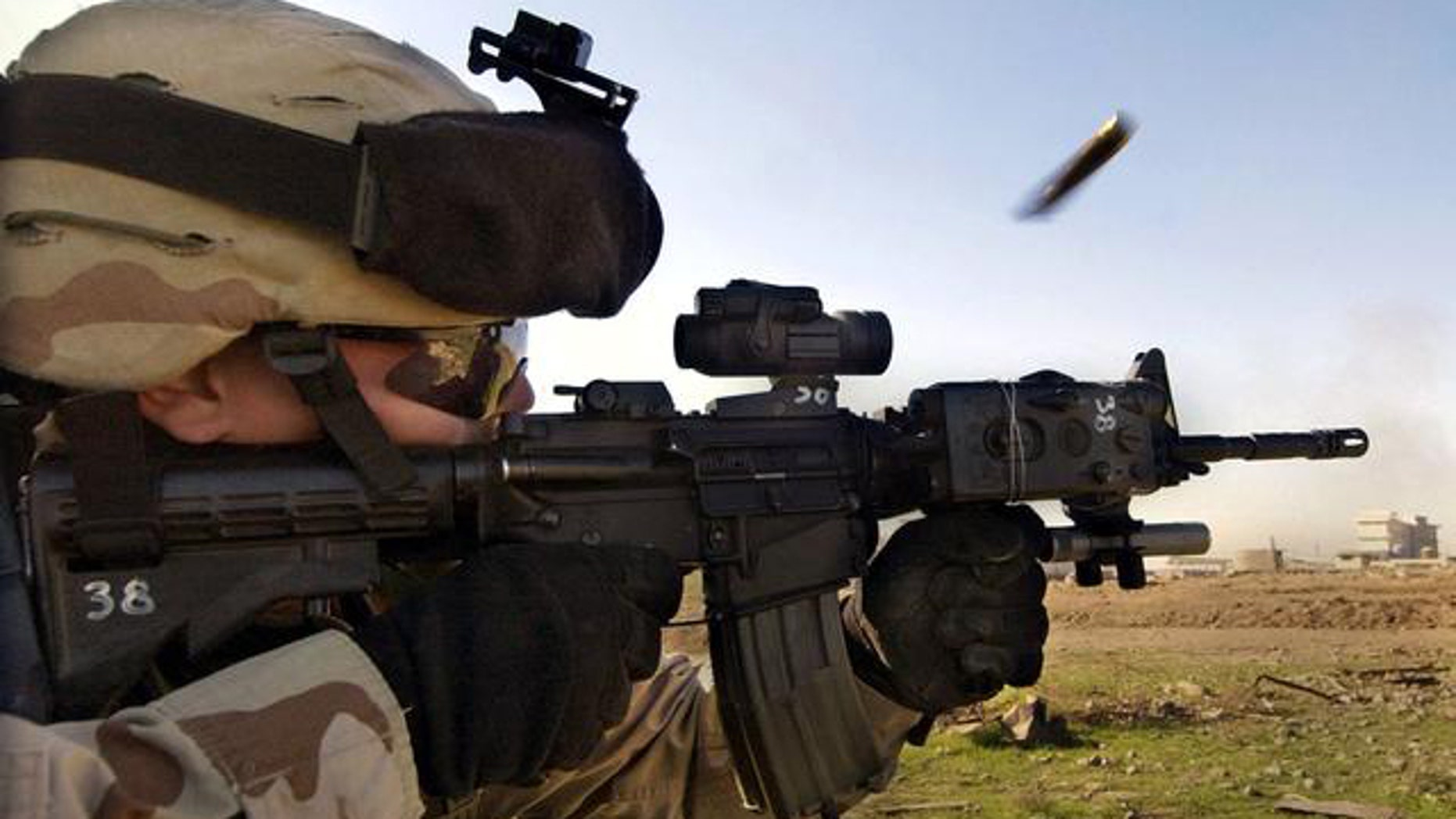 In this December 2004 file photo, a U.S. Army soldier fires a rifle during a fight with insurgents in Mosul, Iraq.