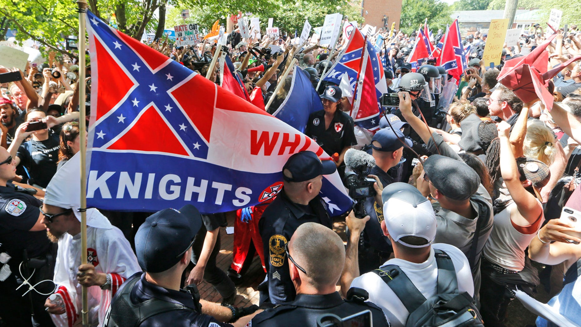 This July 8, 2017 photo shows members of the KKK escorted by police past a large group of protesters during a KKK rally in Charlottesville, Va.