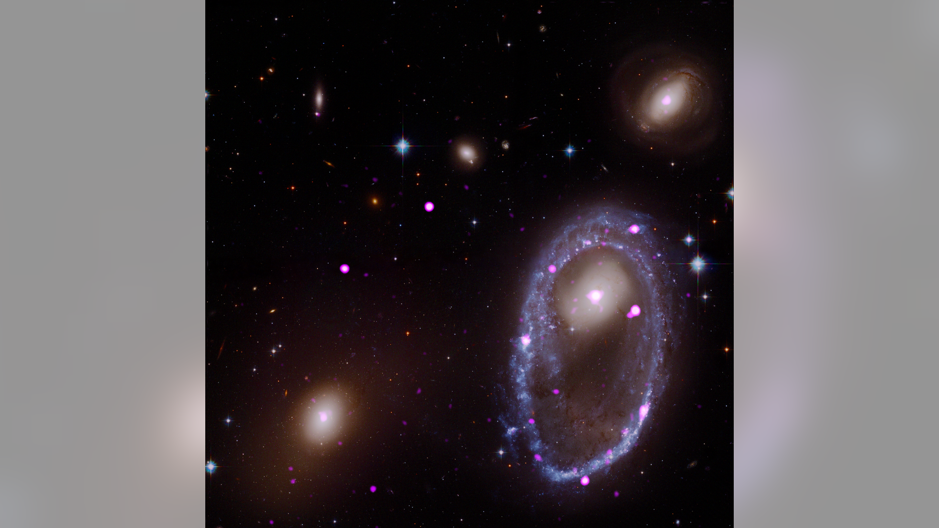 A composite image of the ring galaxy AM 0644-741. The image includes X-ray data from the Chandra X-ray Observatory (purple) and optical data from NASA's Hubble Space Telescope (red, green and blue). The galaxy AM 0644 is located in the lower right.