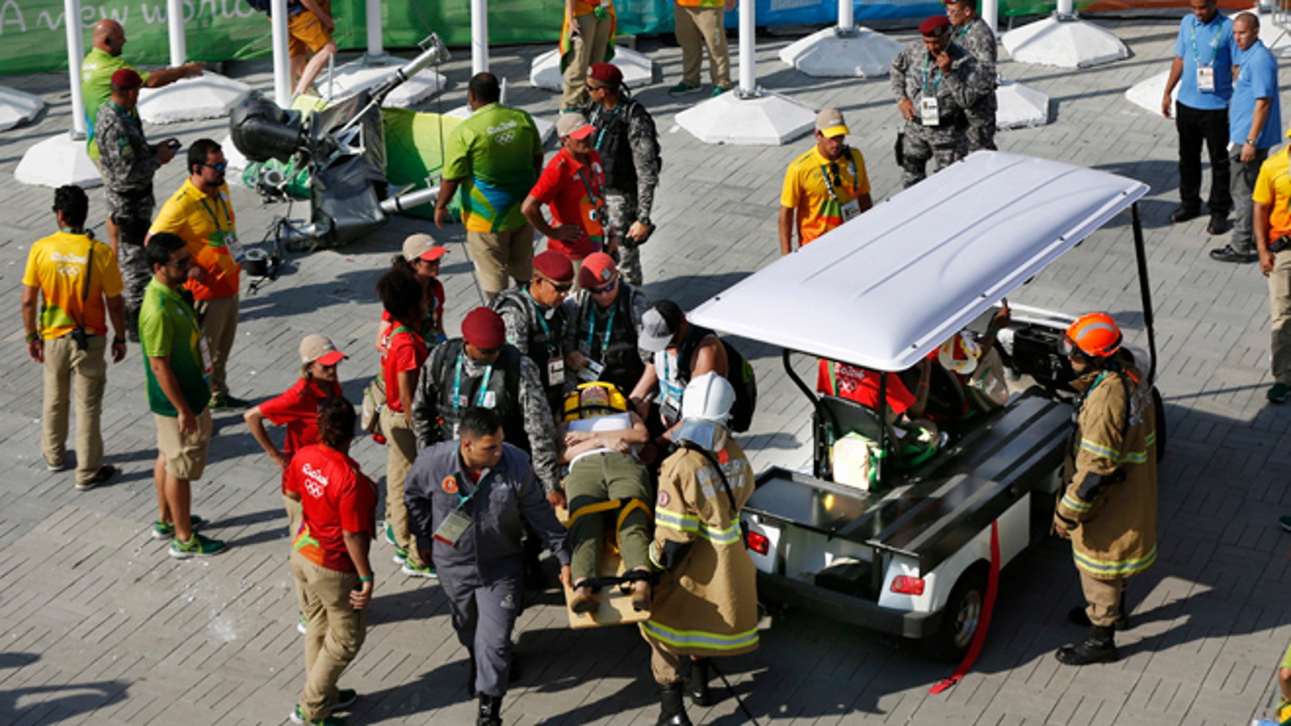 An injured woman is taken away on a backboard after being struck by an overhead television camera, laying top left, that fell from the wires suspending it over Olympic Park during the Summer Games in Rio de Janeiro, Brazil, Monday, Aug. 15, 2016.