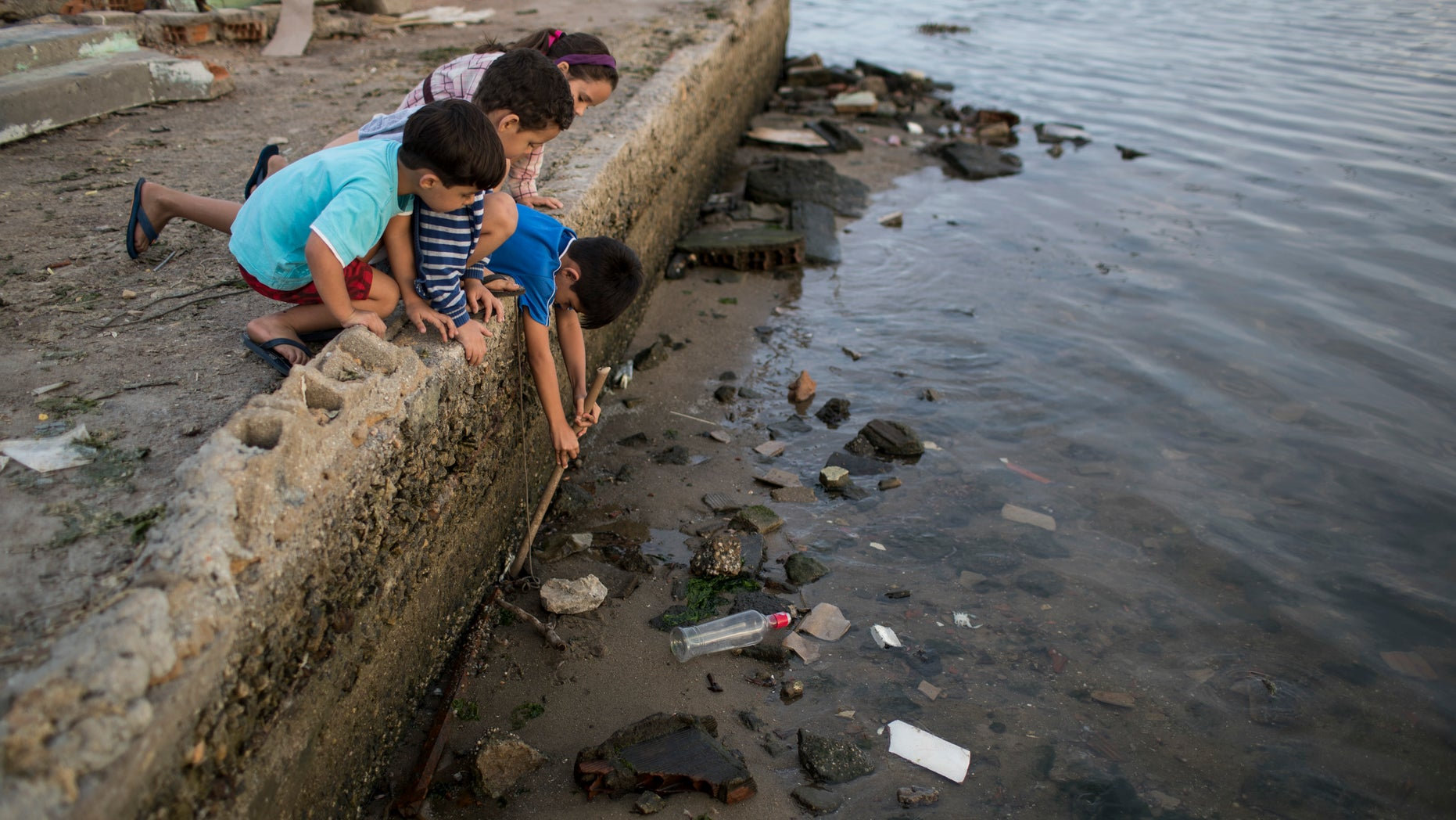 Children try to catch a crab as they play on the polluted shore of Guanabara Bay in Rio de Janeiro, Brazil, Saturday, July 30, 2016. In Rio, the main tourist gateway to the country, a centuries-long sewage problem that was part of Brazil's colonial legacy has spiked in recent decades in tandem with the rural exodus that saw the metropolitan area nearly double in size since 1970. (AP Photo/Felipe Dana)