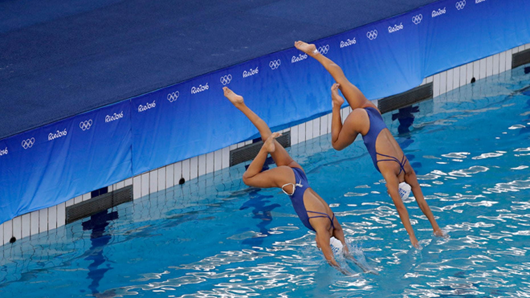 Greece's synchronized swimming duets team of Evangelia Papazoglou and Evangelia Platanioti dive into the pool in the Lenk Aquatic Center during a training session the morning after the pool went through a change in water, on Sunday, Aug. 14, 2016 in Rio de Janeiro, Brazil.