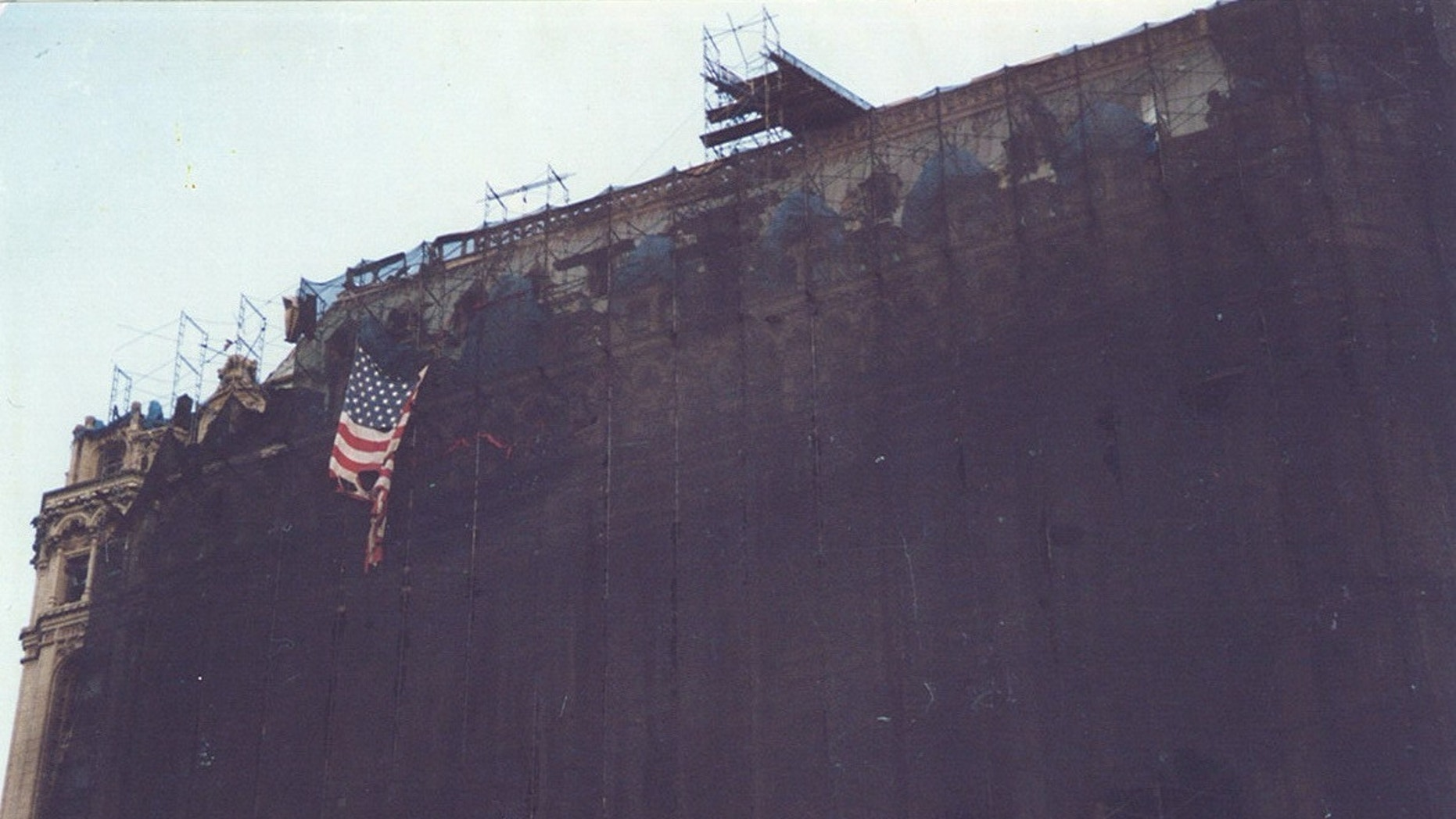 The national 9/11 flag was nearly destroyed by the terror attacks on September 11th 2001 in New York City. In this picture,the flag hangs from the scaffolding of a building just south of Ground Zero.