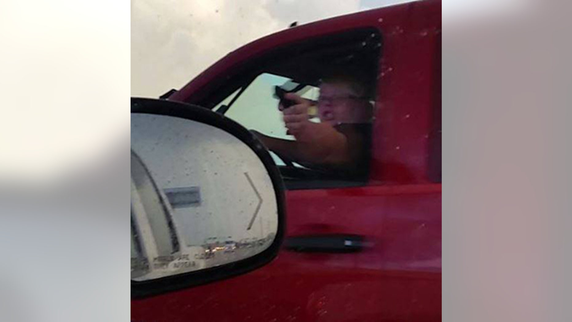 A woman identified as Amanda Downs points a folding knife cast to resemble a gun at fellow motorist in La Porte, Texas August 2.