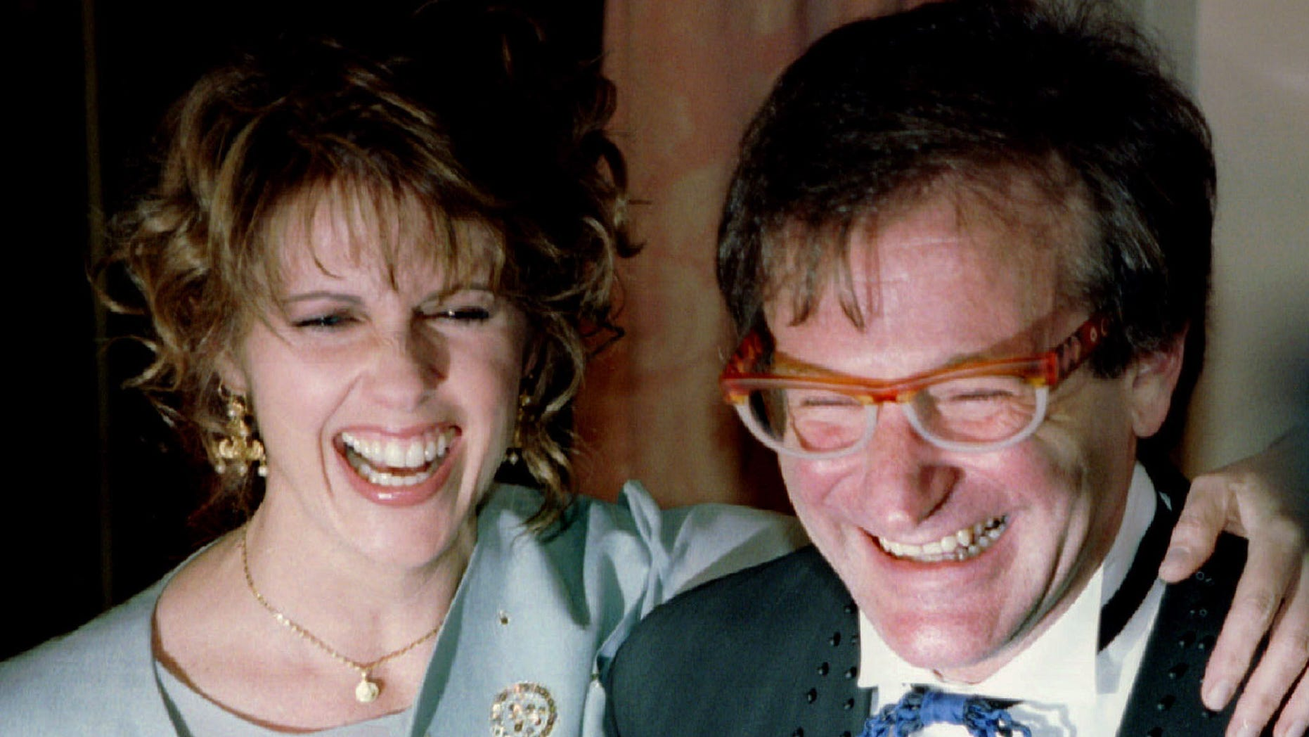 """Actress Pam Dawber (L) shares a laugh with actor Robin Williams as they pose for photographers before the annual American Museum of the Moving Image Tribute dinner February 23, 1995 in New York. Williams and Dawber stared in the TV show """"Mork and Mindy"""". Williams is this years honoree at the tribute  REUTERS/Jeff Christensen - RTXG84Q"""