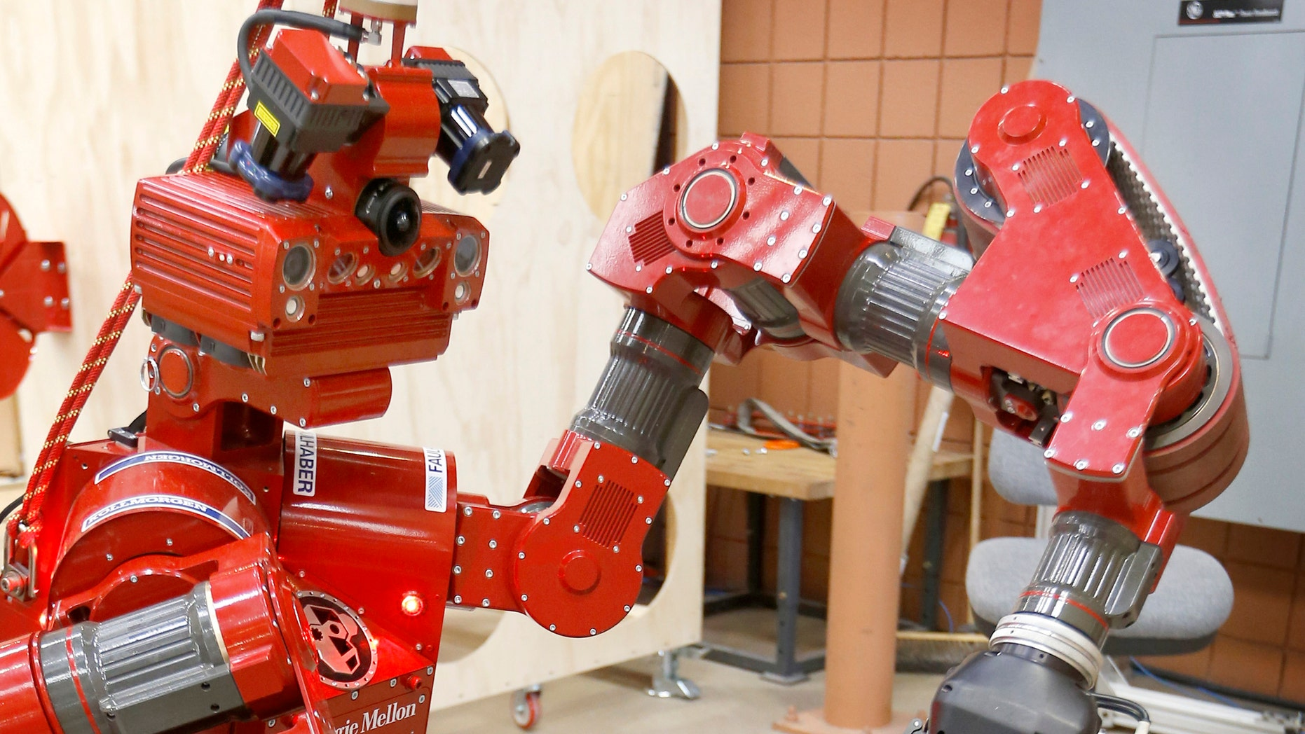 In this Wednesday, Dec. 11, 2013 photo, the CMU Highly Intelligent Mobile Platform robot, known as CHIMP, (CMU Highly Intelligent Mobile Platform) is put through some paces as it is switching the hold of a fire hose from one grasping unit to another at the National Robotics Engineering Center in Pittsburgh. Carnegie Mellon researchers are testing the new search-and-rescue robot that will compete in the U.S. Defense Department's upcoming national robotics competition in Florida. Competitors from other schools and companies will be vying for a $2 million U.S. Defense Department prize. (AP Photo/Keith Srakocic)