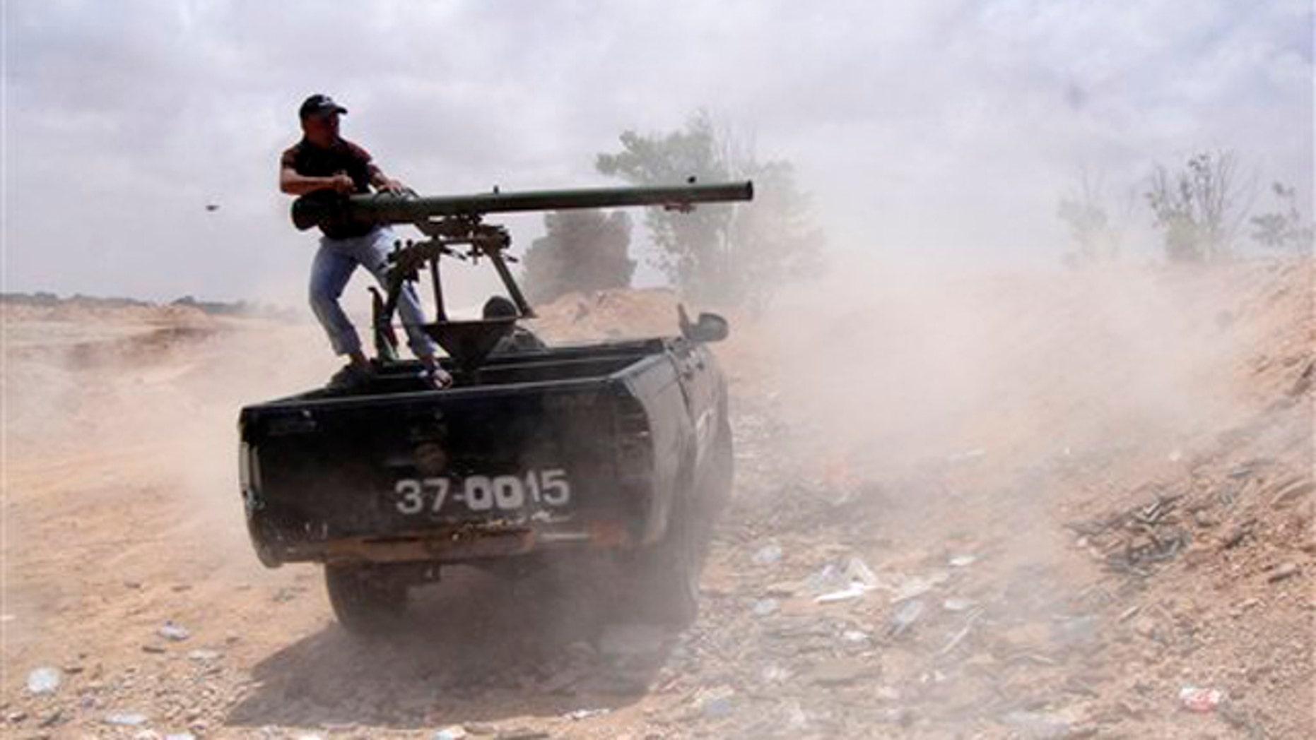Libyan rebel fires a rocket toward pro-Muammar Qaddafi forces on the front line of Dafniya in Misrata, Libya, June 21.