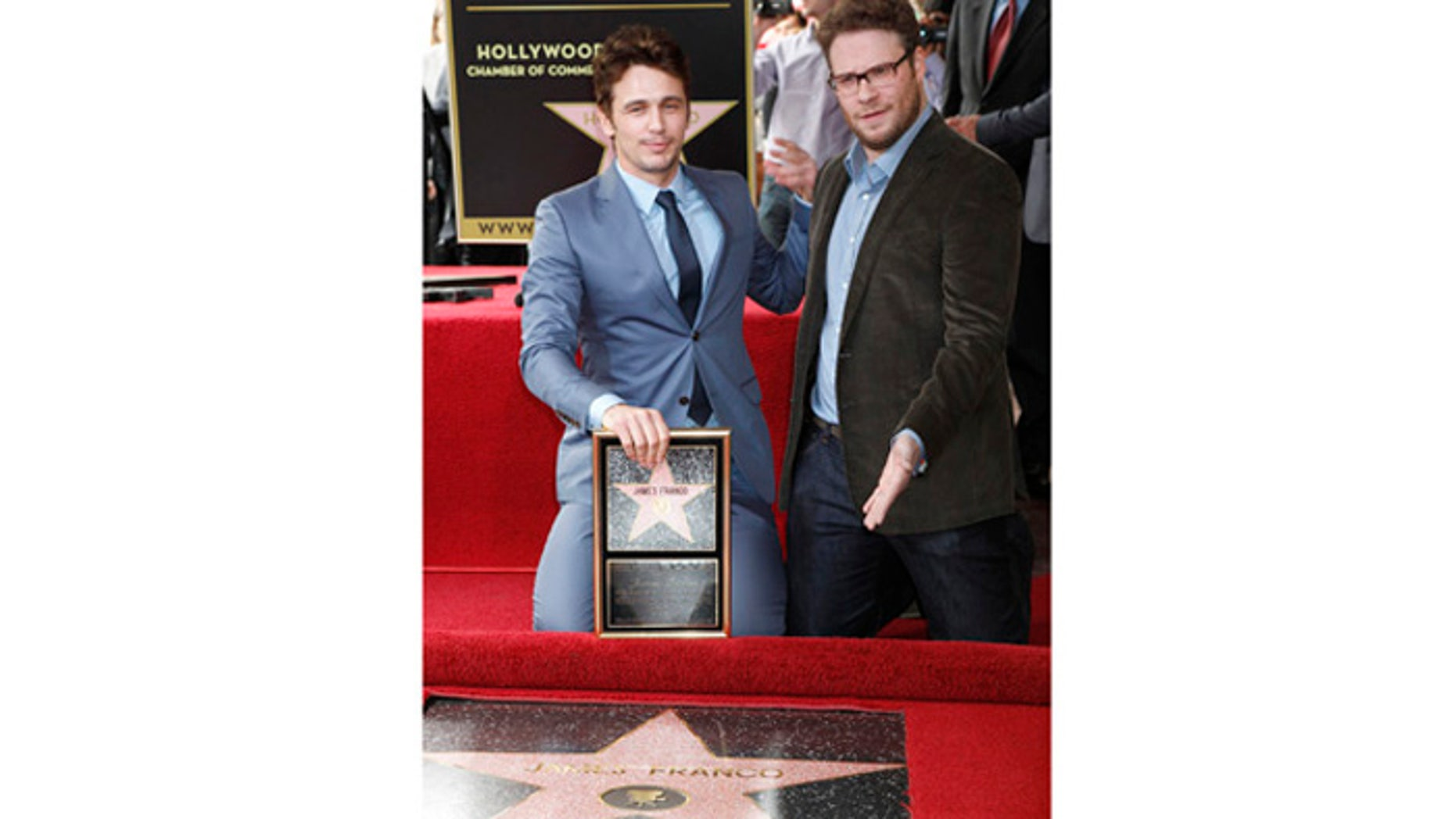 Actor James Franco (L) poses with his newly unveiled star on the Hollywood Walk of Fame, with actor Seth Rogen March 7, 2013. REUTERS/Fred Prouser (UNITED STATES - Tags: ENTERTAINMENT) - RTR3EPGG