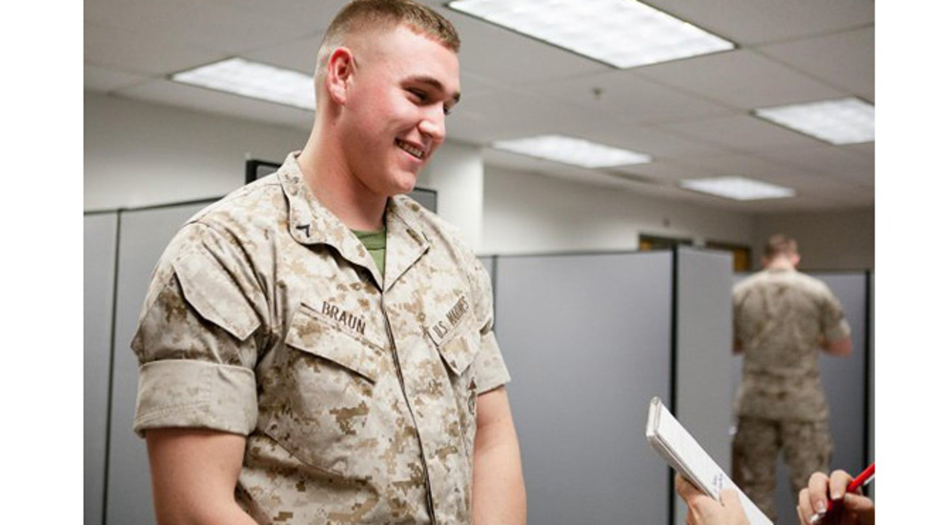 Marine Pfc. Austin Braun talks to a reporter about rolling sleeves at Fort Myer, Va., in 2014. (U.S. Army)