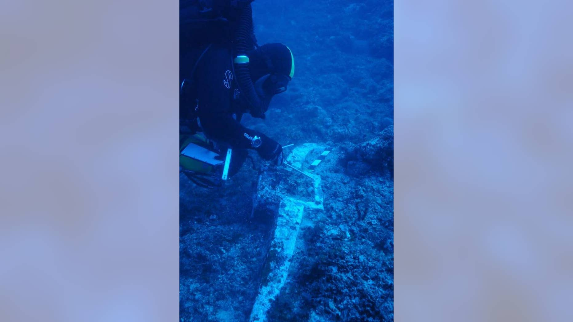 Here a researcher examines the anchor of what may be the Antikythera wreck or another wreck nearby. They are uncertain because they used Costeau's Antikythera expedition videos to gauge where to anchor their boat. Since some of the shots in the