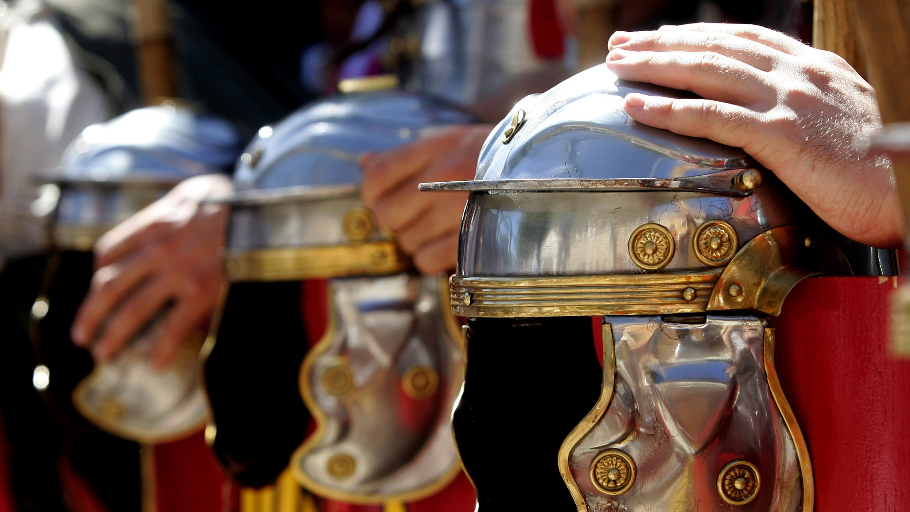 File photo - Actors, dressed as a Roman pretorian guards, hold their helmets at a parade during a show reviving the ancient Roman circus in the central Spanish village of Banos de Valdearados August 22, 2004. (REUTERS/Felix Ordonez)