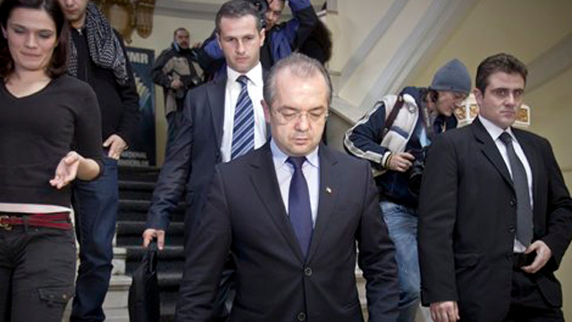 Feb. 6, 2012: Romanian Premier Emil Boc, front center, leaves the headquarters of the ruling Democratic Liberal party in Bucharest, Romania, after announcing his immediate resignation with his government on Monday, saying he wanted to protect the stability of the country.