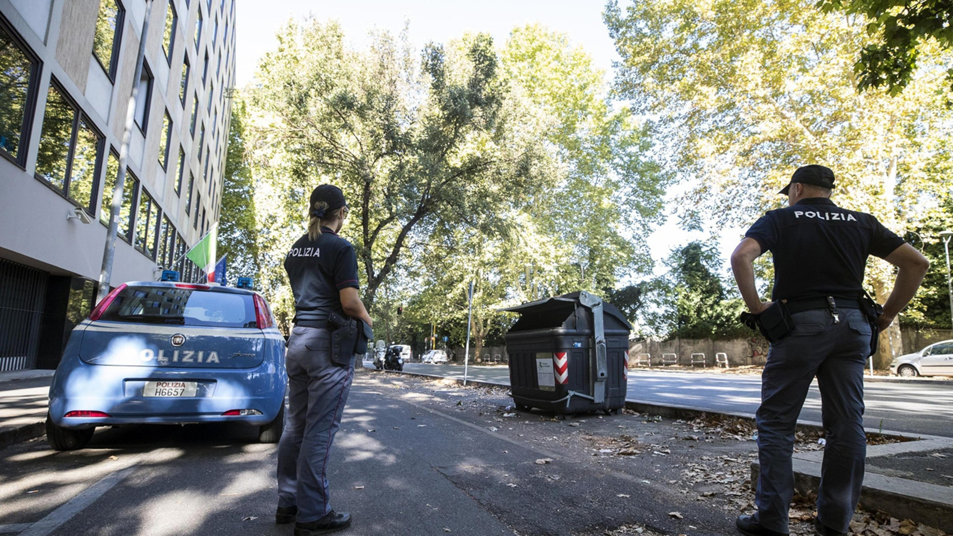 Police officers stand near the site where a trash bin was removed after two amputated legs were found in Rome.