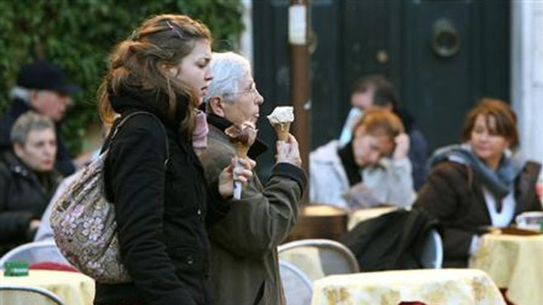 Italians eating gelato ice-cream while passing diners at Campo di Fiori in Rome.  Tourist and other visitors can now face fines for snacking at the city's historic sites.