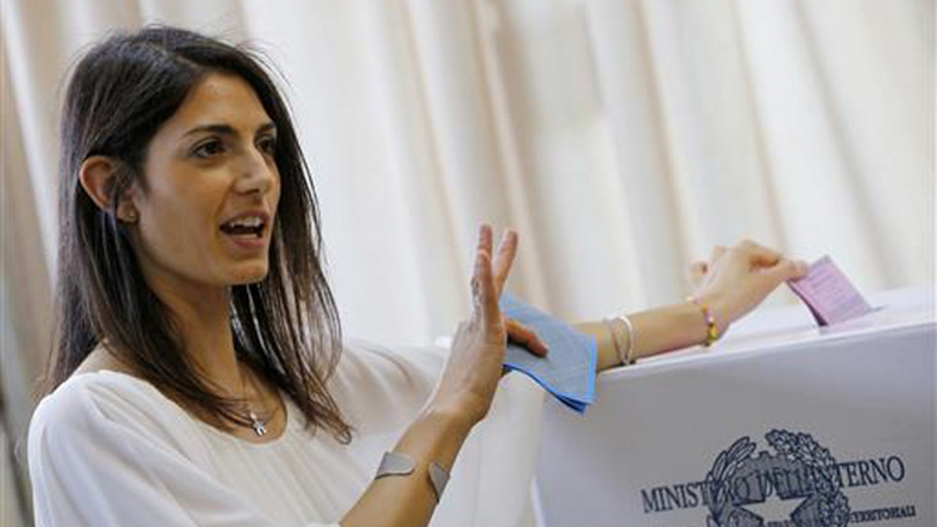 Anti-establishment 5-Star Movement (M5S) candidate as Rome's mayor Virginia Raggi poses for photographers as she casts her ballot in polling station in Rome, Sunday, June 19, 2016.