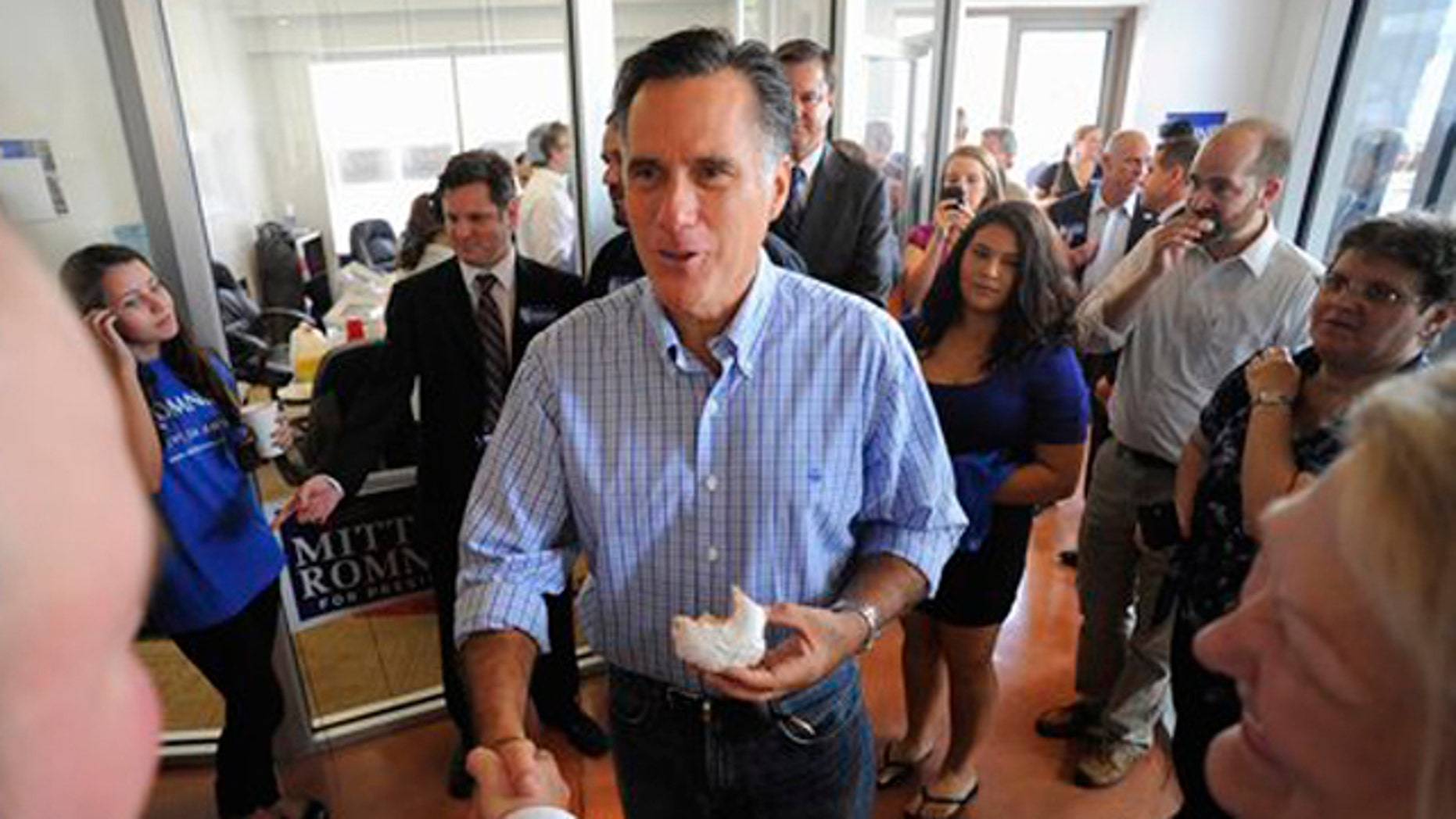 Former Massachusetts Gov. Mitt Romney meets with campaign staffers and supporters as he tours his new Florida campaign headquarters in Tampa, Fla., Sept. 2.