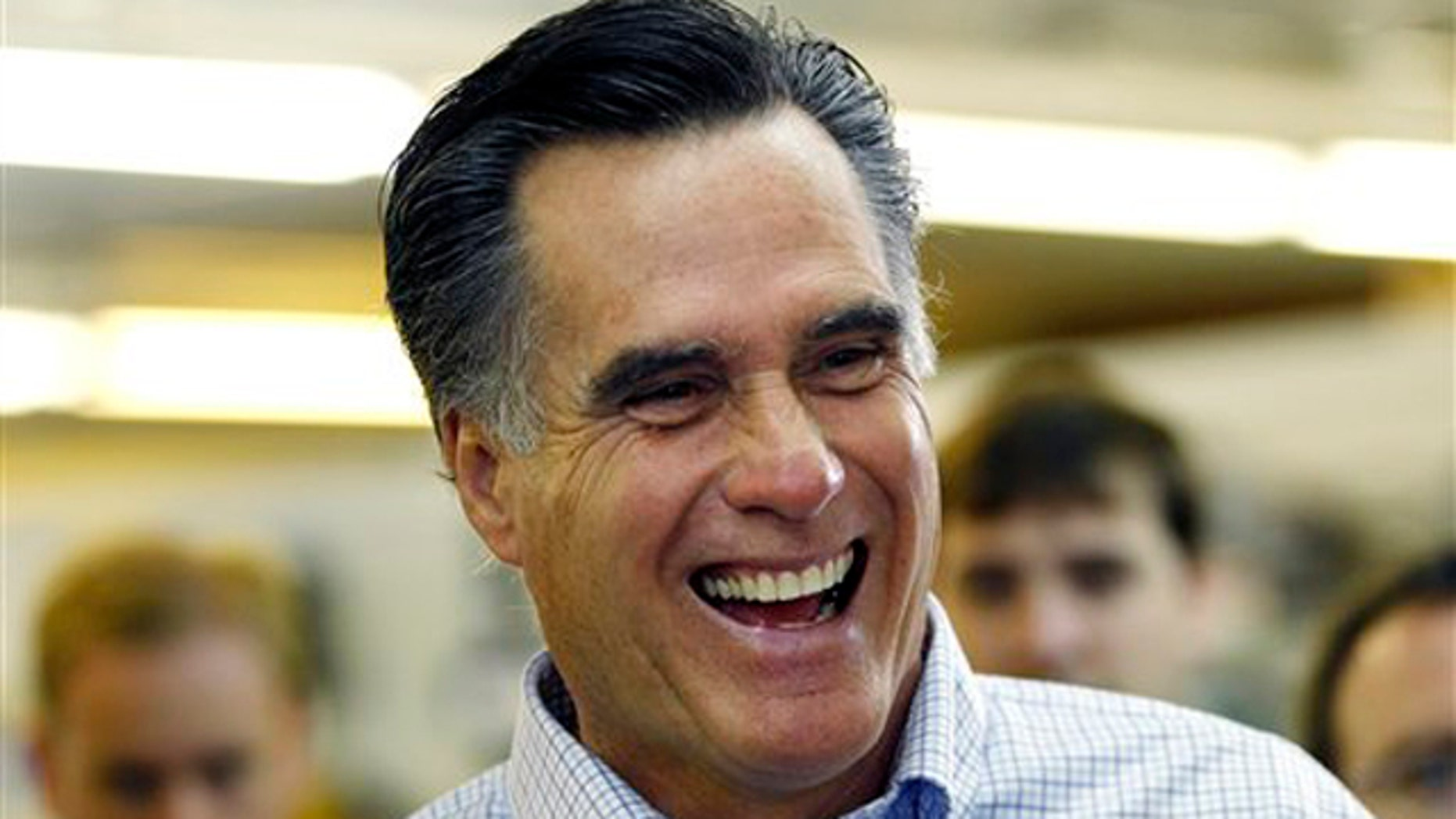 Former Massachusetts Gov. Mitt Romney laughs during a campaign stop at a hardware store in Derry, N.H., June 14.