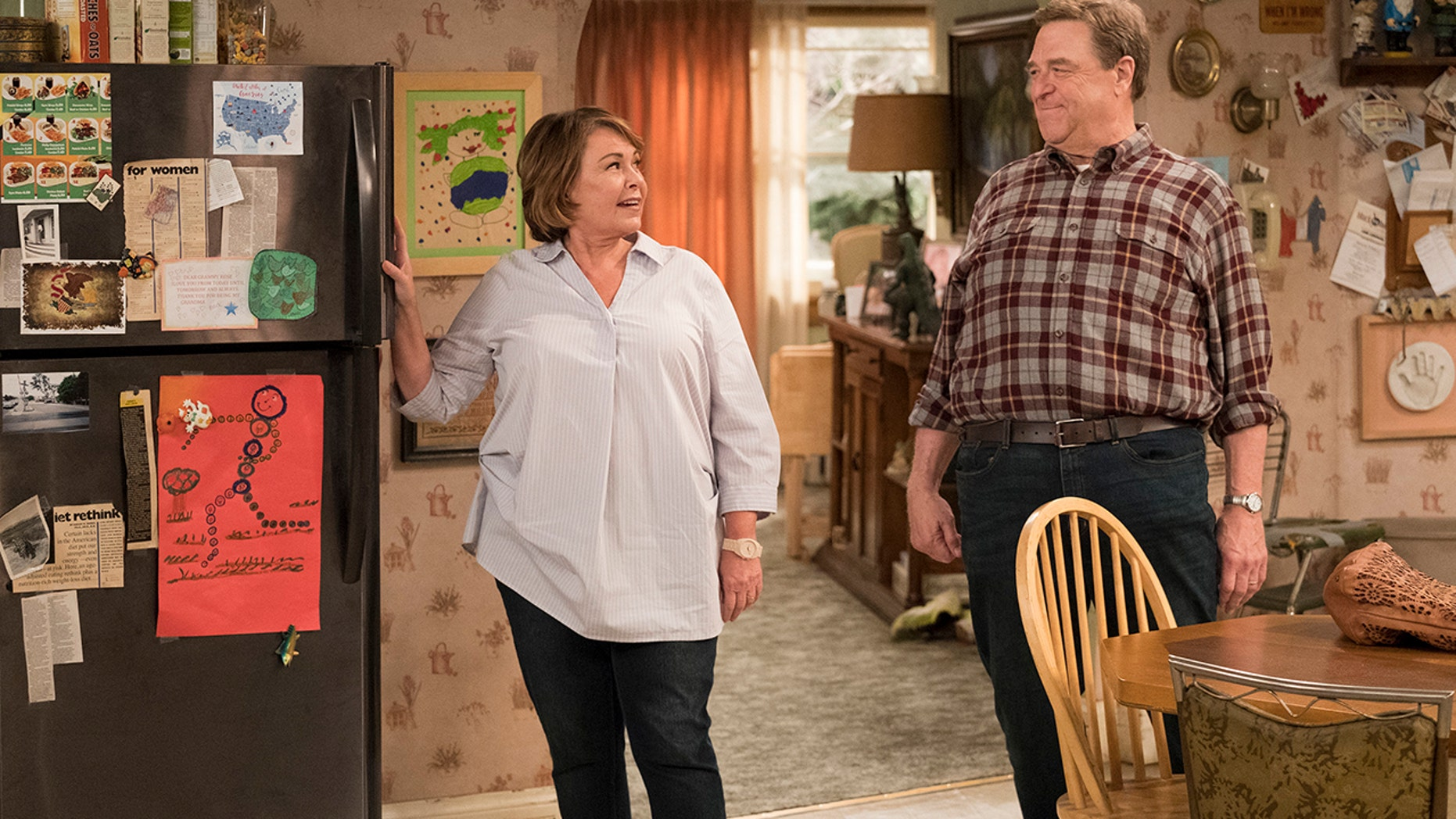 """This image released by ABS shows Roseanne Barr, left, and John Goodman in a scene from the comedy series """"Roseanne."""" ABC's """"Roseanne"""" revival is in the running for Emmy nominations Thursday, but will TV academy voters overlook its star's racist tweet that brought the sitcom to an abrupt end?"""