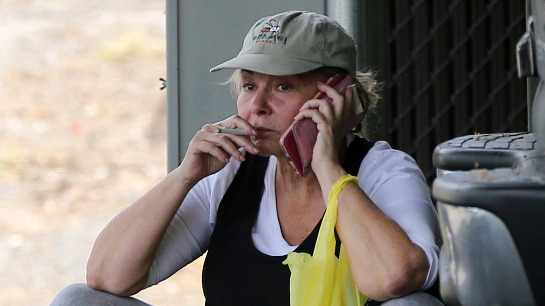 The visibly stressed Roseanne is seen sitting on a curb in a hat, cuffed jeans and flip flops talking a phone call while smoking a cigarette.