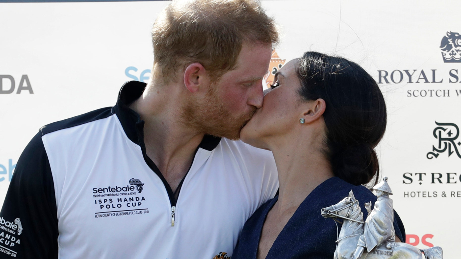 Meghan, Duchess of Sussex and Britain's Prince Harry kiss during the presentation ceremony for the Sentebale ISPS Handa Polo Cup at the Royal County of Berkshire Polo Club in Windsor, England, Thursday, July 26, 2018.(AP Photo/Matt Dunham)
