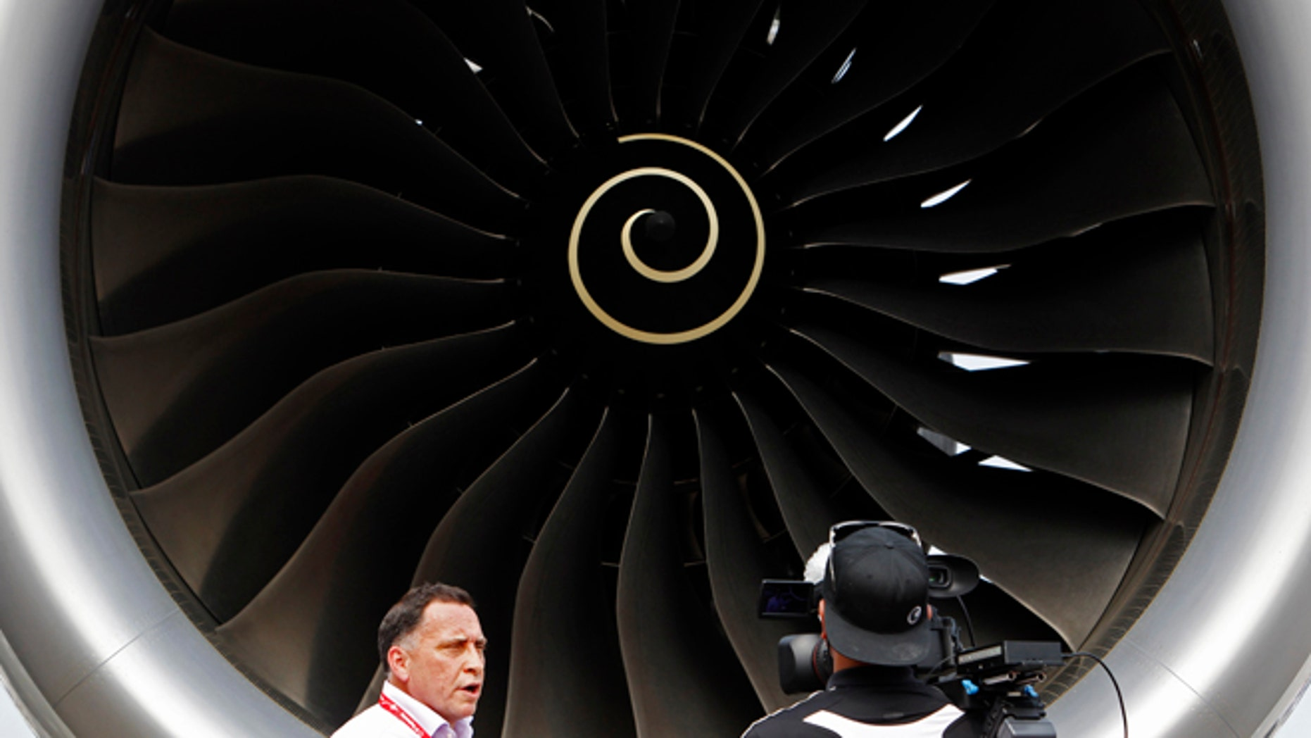 Feb. 11, 2014: Journalists work next to the Rolls Royce engine of an Airbus A350 on display at the Singapore Airshow.