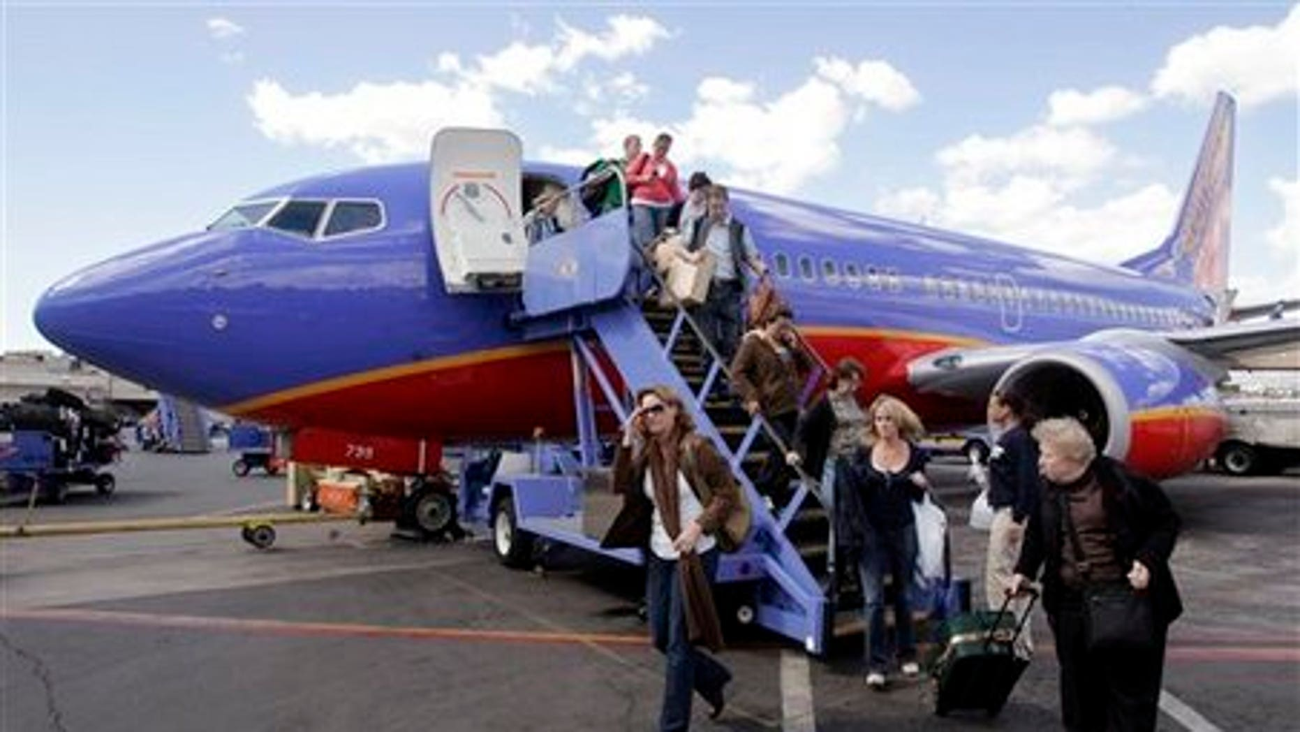 d6e3f9088c60 Passengers disembark a Southwest plane with carry-on luggage.