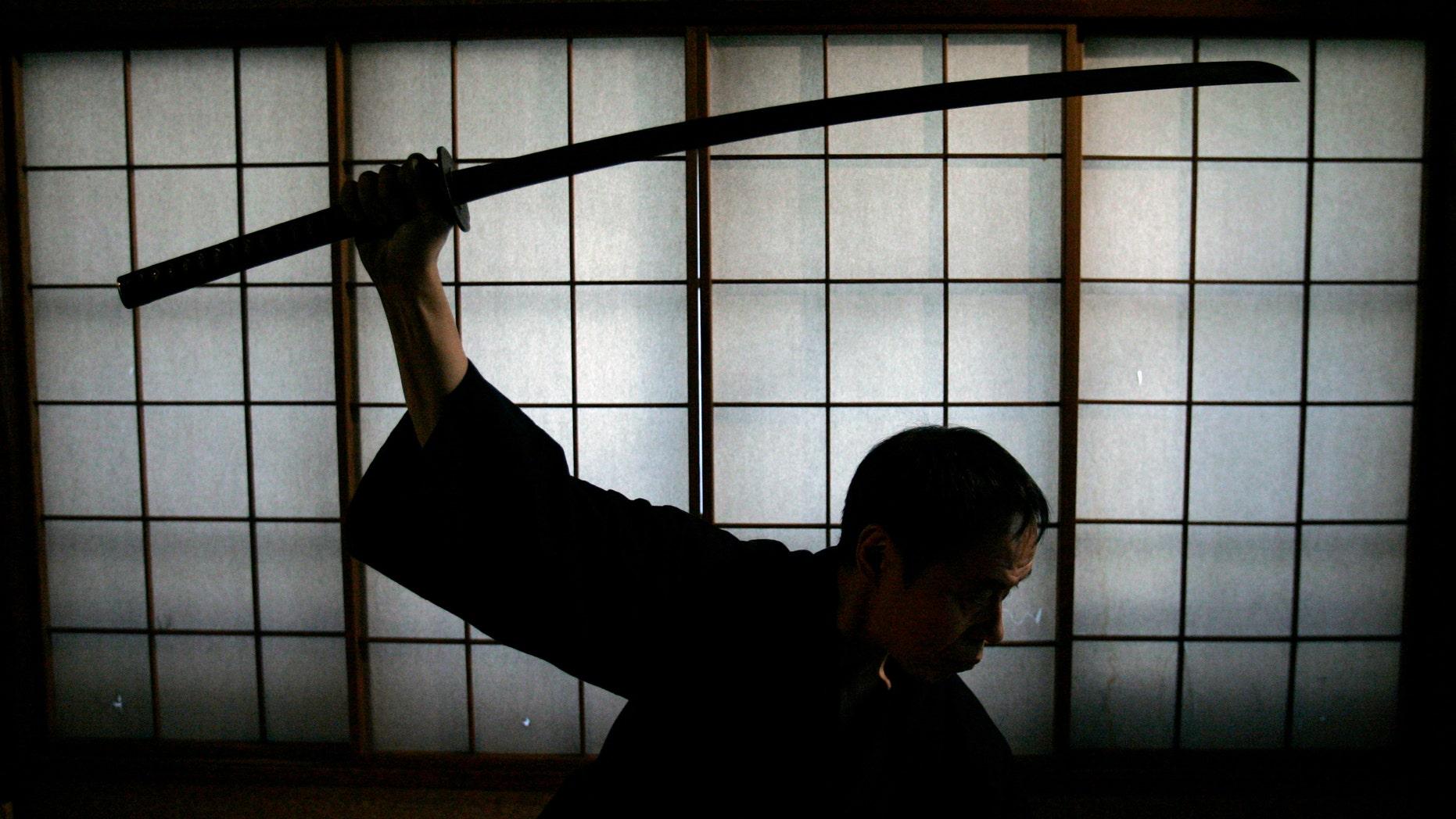 Japanese man holds a samurai sword. (Reuters)