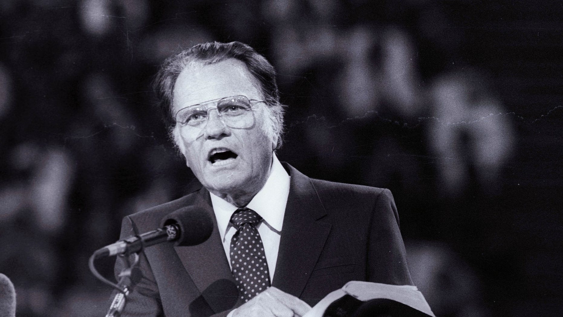 FILE -- US evangelist Billy Graham preaches the Gospel to thousands of believers during tonight's meeting at Bercy's Stadium in Paris as part of a worldwide crusade, September 20, 1986.
