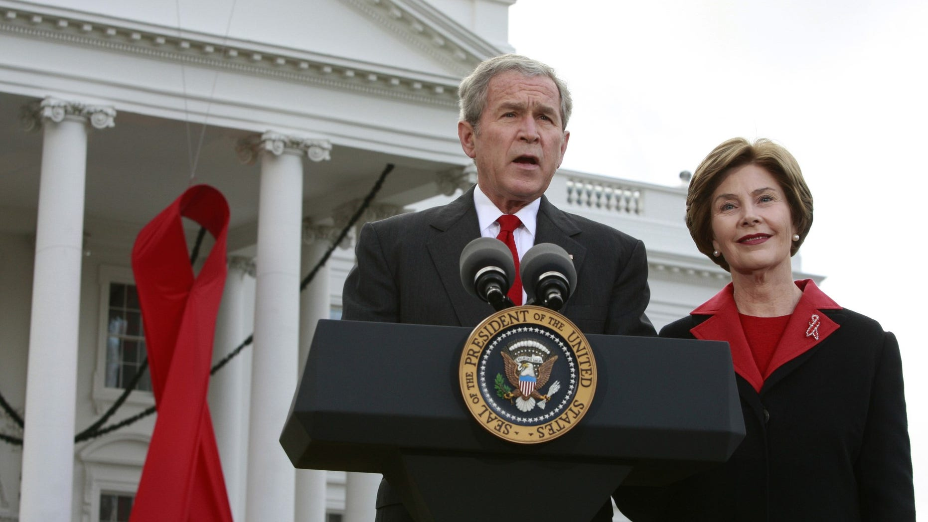 FILE -- Former President George W. Bush speaks alongside a giant red AIDS ribbon on the occasion of World AIDS day with first lady Laura Bush on the North Lawn of the White House in Washington December 1, 2008.