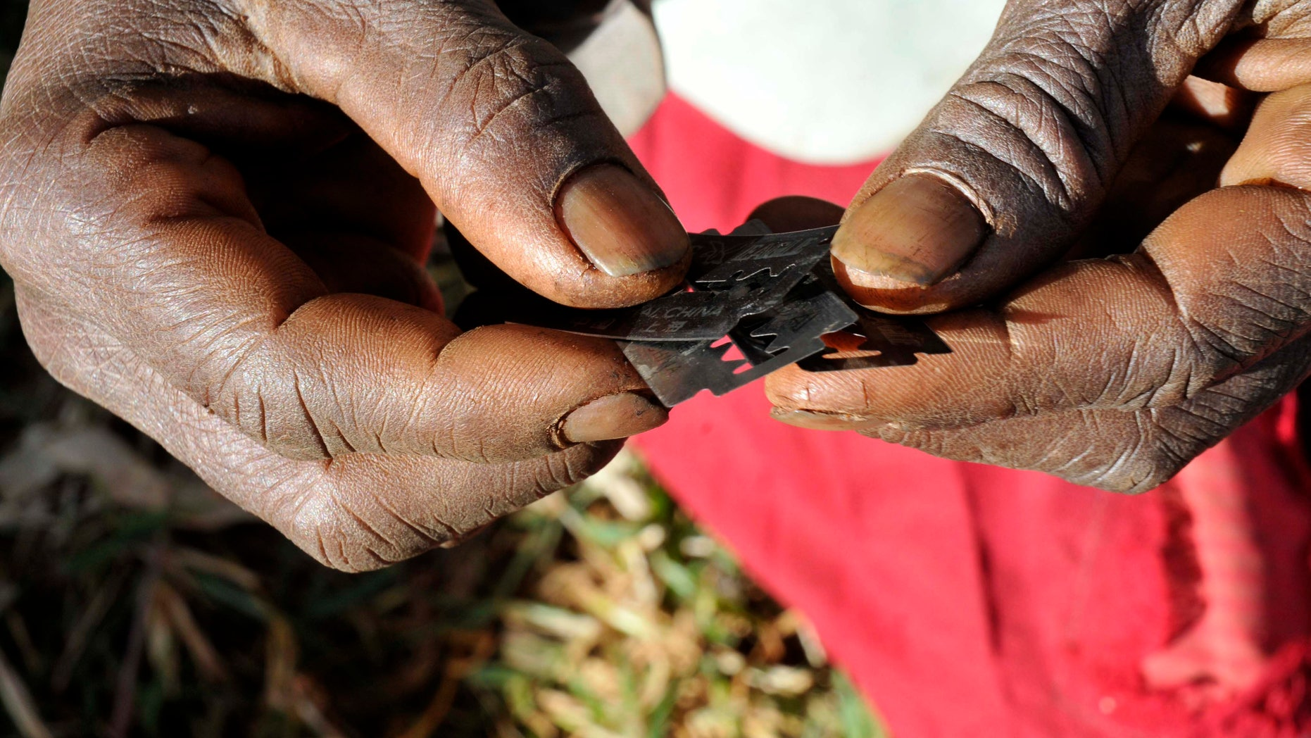 Prisca Korein, a 62-year-old traditional surgeon, holds razor blades before carrying out female genital mutilation on teenage girls from the Sebei tribe in Bukwa district, about 357 kms (214 miles) northeast of Kampala, December 15, 2008. The ceremony was to initiate the teenagers into womanhood according to Sebei traditional rites.