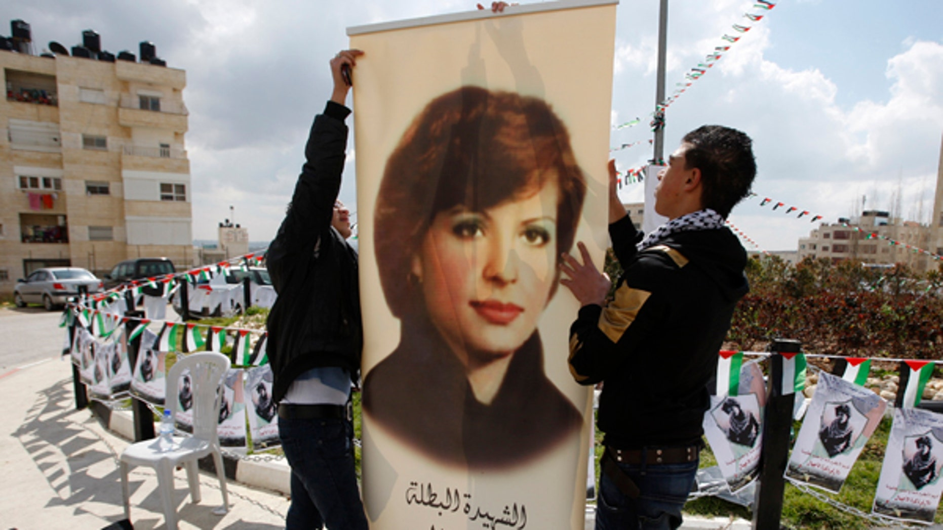 Palestinians in the West Bank town of Al-Bireh decorate a town square with a poster depicting Dalal Mughrabi. The United Nations and Norway have recently taken issue with a women's center being named after the terrorist responsible for one of the largest terror attacks in Israel's history.