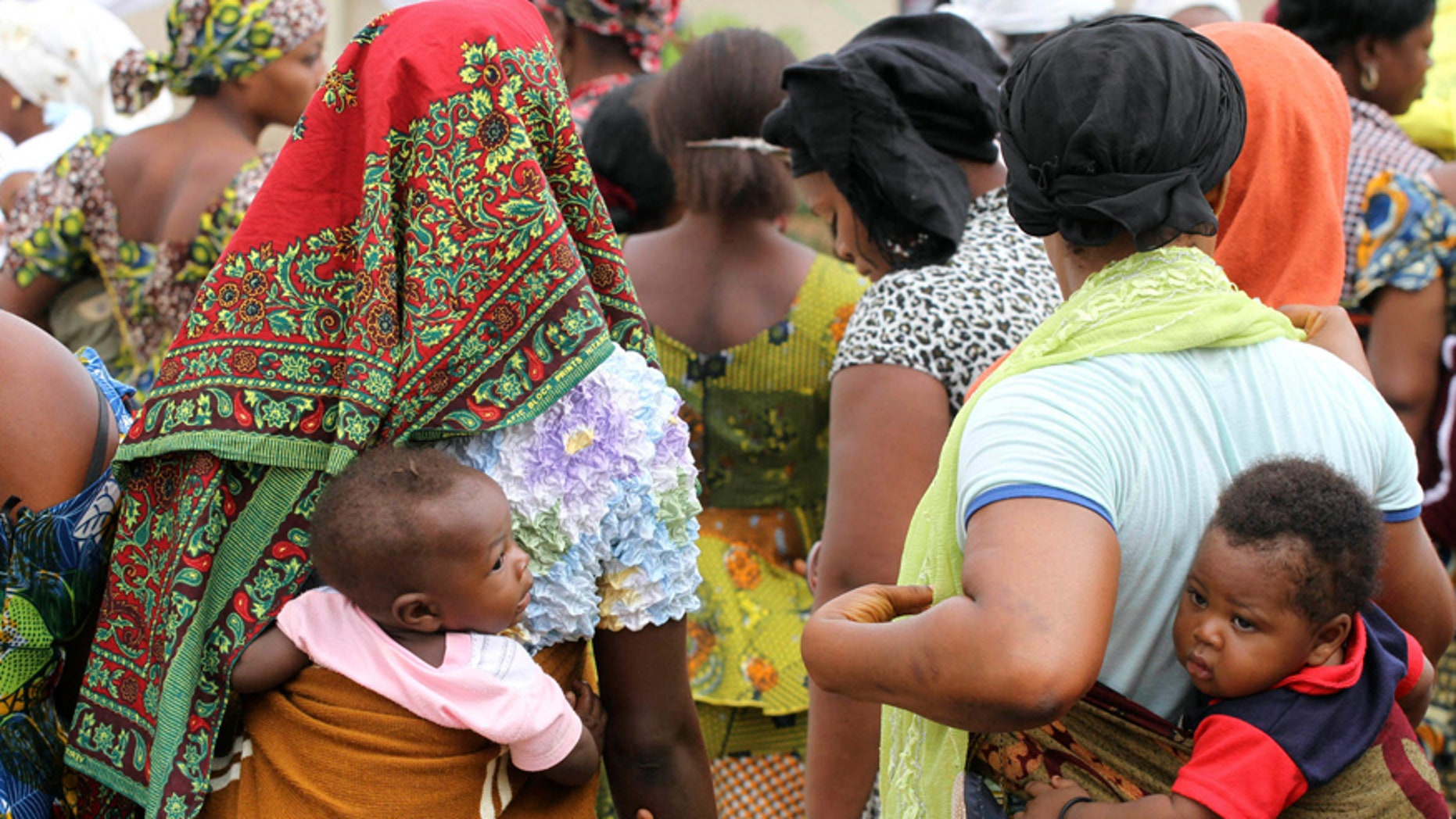 Women carry their children wait for the arrival of U.N. Secretary General Ban Ki-moon for the unveiling of a primary health care clinic in Dutse Makaranta village, on the outskirt of Nigeria's capital, Abuja May 23, 2011. REUTERS/Akintunde Akinleye(NIGERIA - Tags: POLITICS HEALTH) - RTR2MSO1