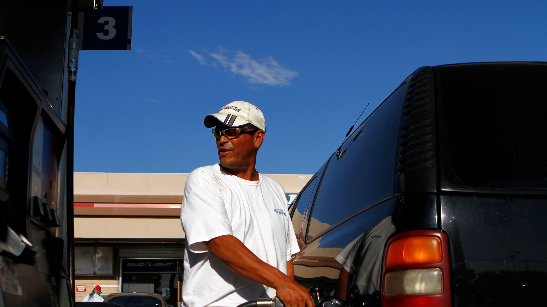 FILE --  August 2011: A motorist pumps fuel into his vehicle at JJ's Express Gas Plus station in Phoenix gas station in Phoenix, Arizona.
