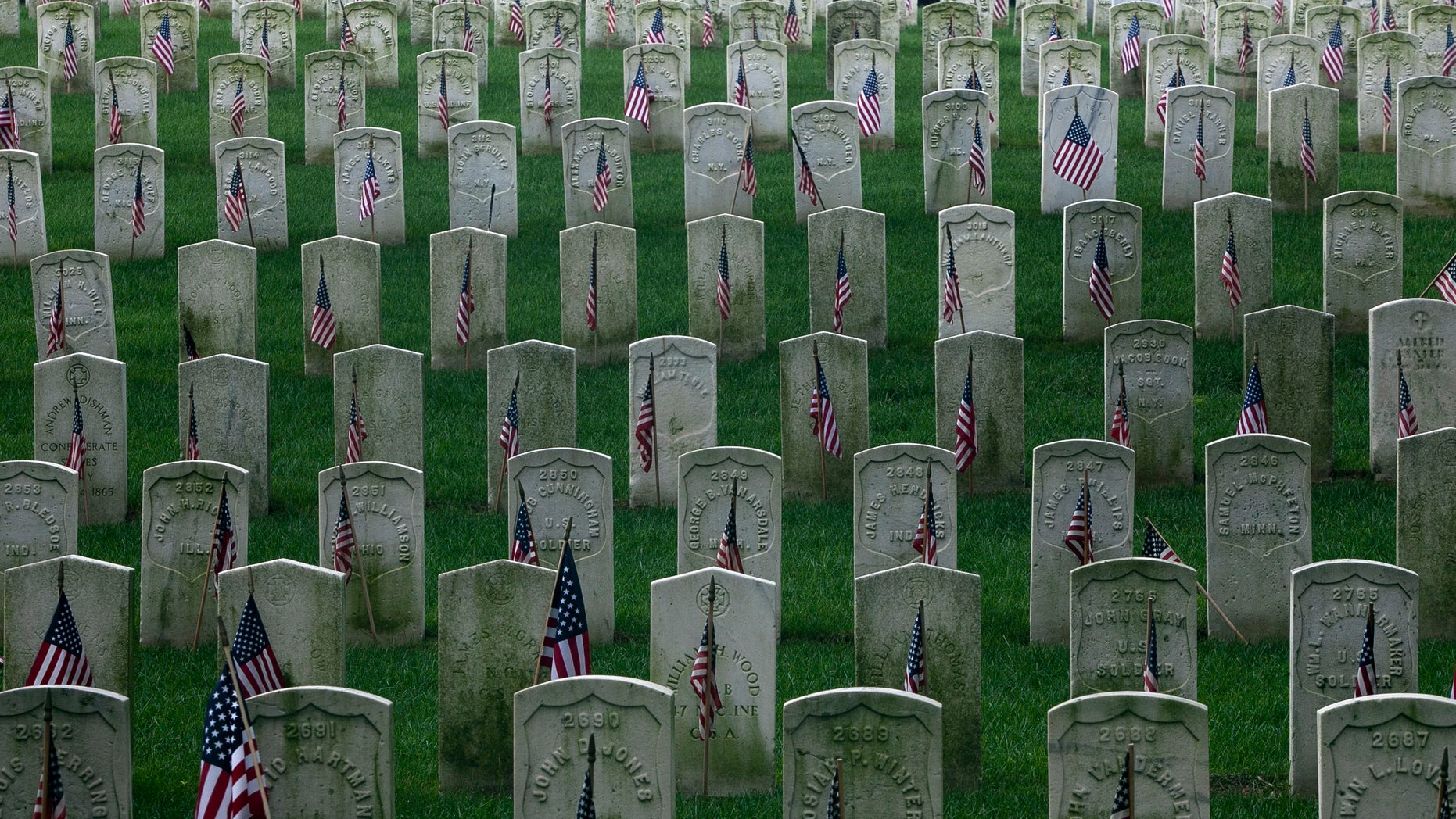 U.S. flags are placed on gravestones of military veterans at the Cyprus Hills National Cemetery in New York May 27, 2012. REUTERS/Allison Joyce (UNITED STATES - Tags: MILITARY SOCIETY CONFLICT) - RTR32Q65