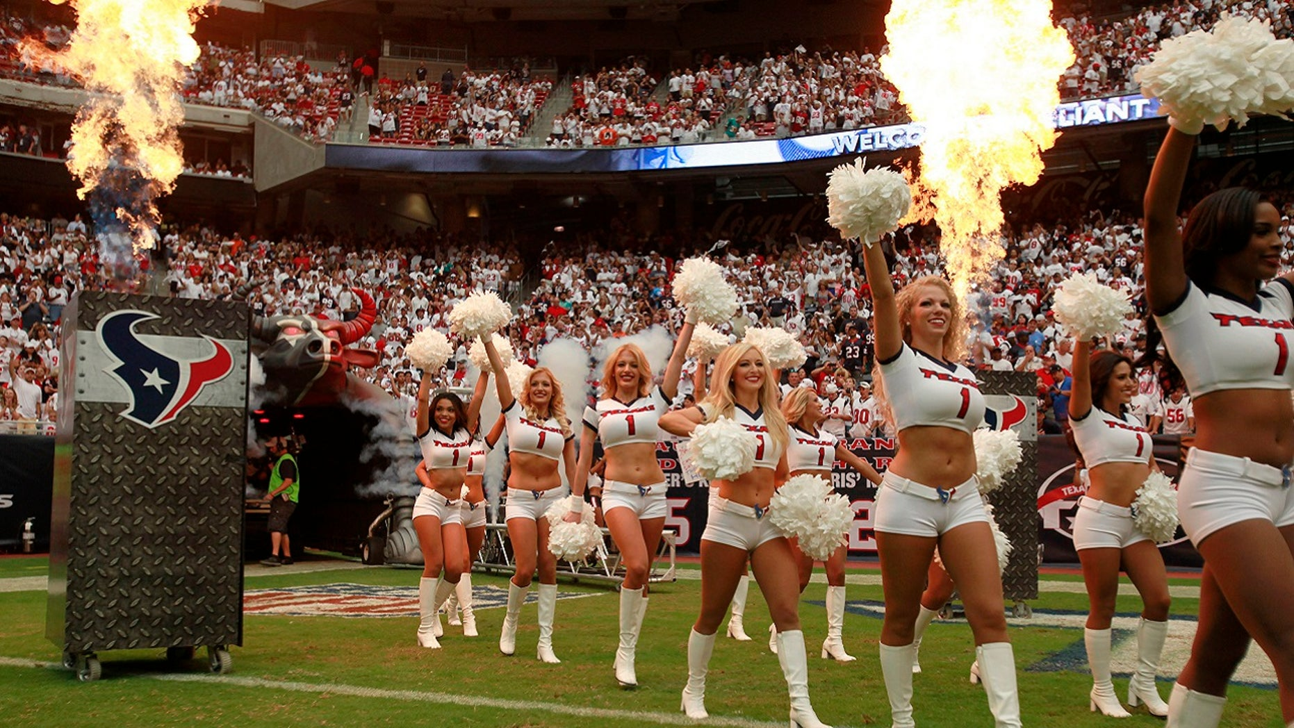 The Houston Texans cheerleaders enter the field surrounded by smoke and flame during the opening ceremonies of the season opening NFL football game against the Miami Dolphins in Houston, Sept. 9, 2012.
