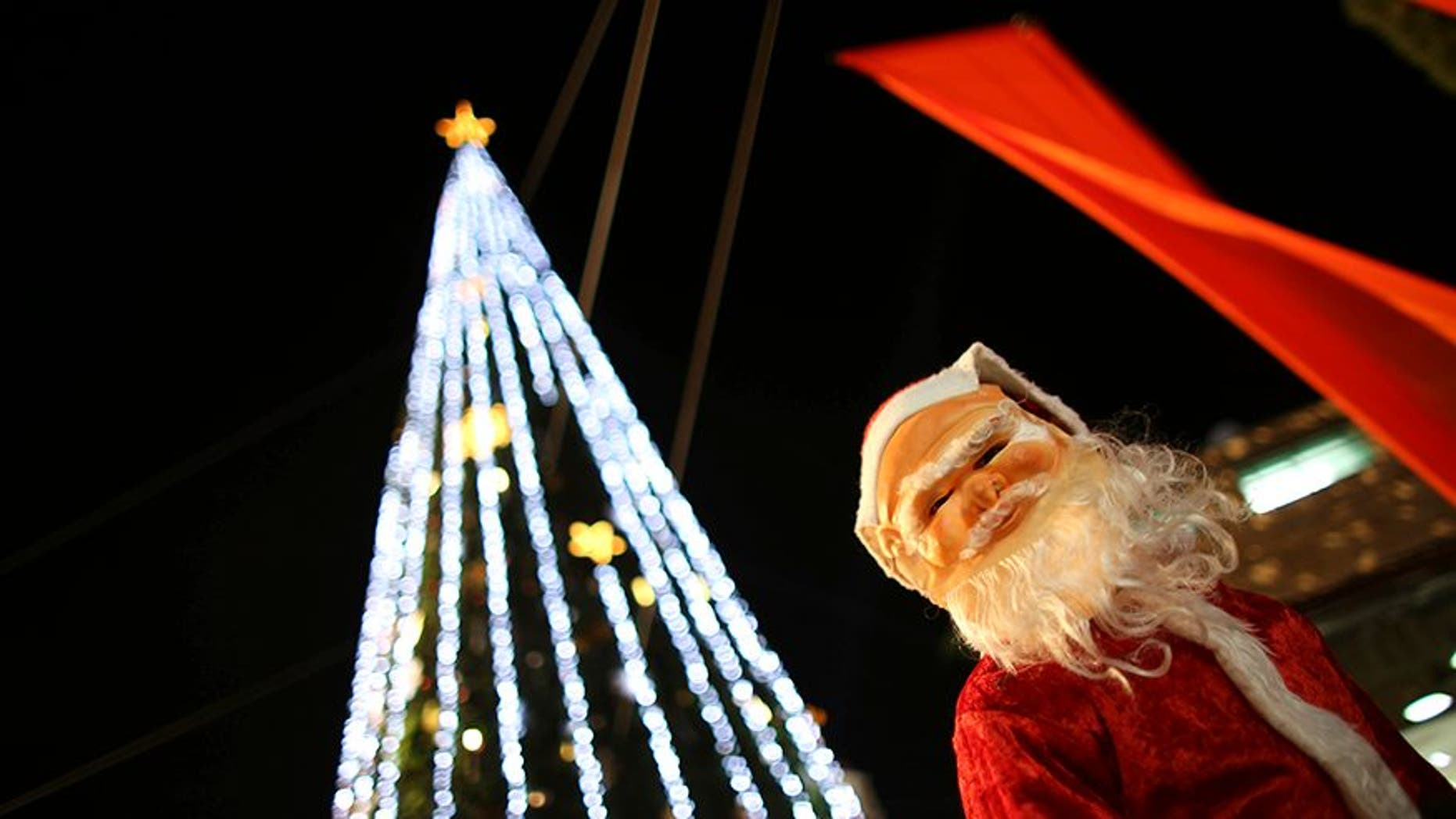 d88d8e7516 A boy wearing a Santa Claus costume attends a Christmas tree lighting  ceremony in the northern