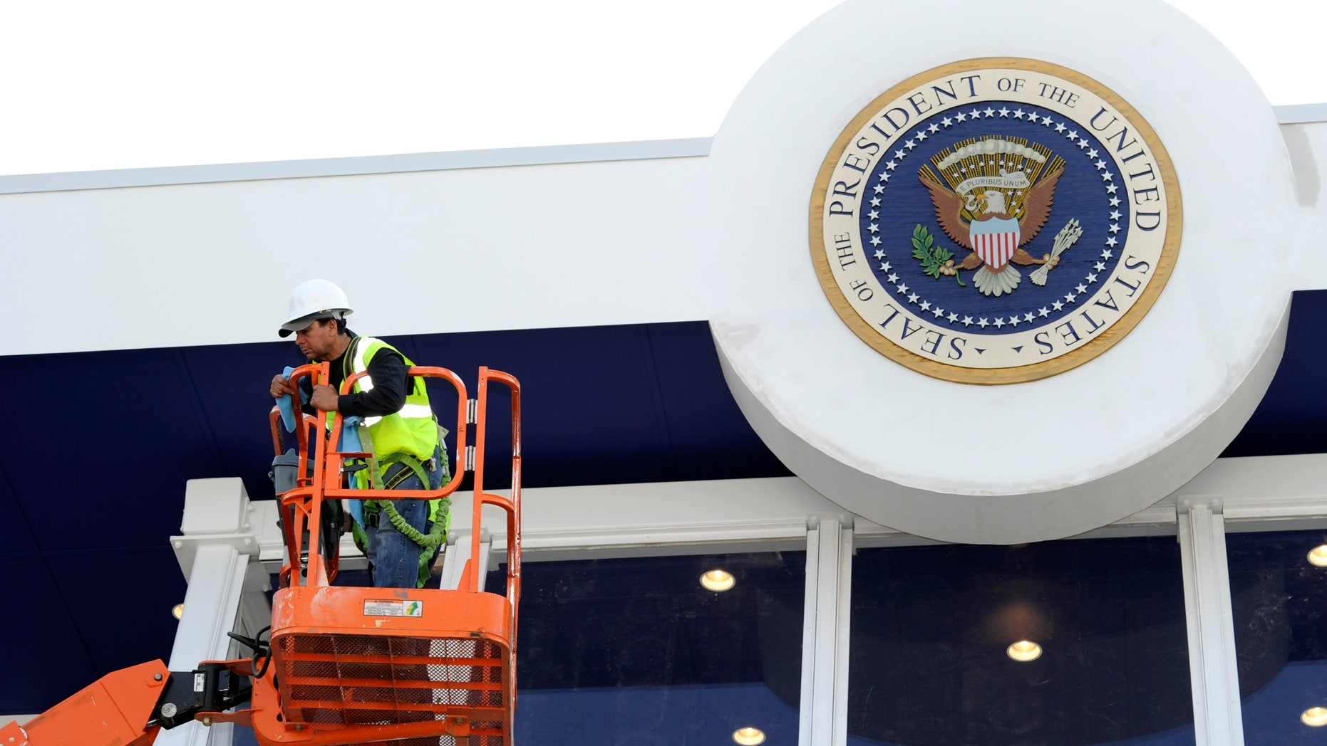 Workers use a hydraulic lift to position themselves to clean the bullet-proof glass under the Seal of the President on the inaugural reviewing stand in front of the White House in Washington January 12, 2013. U.S. President Barack Obama, family and dignitaries will watch the parade from the stand, after the Presidential Inauguration on January 21, 2013.         REUTERS/Mike Theiler (UNITED STATES - Tags: POLITICS) - RTR3CD6F