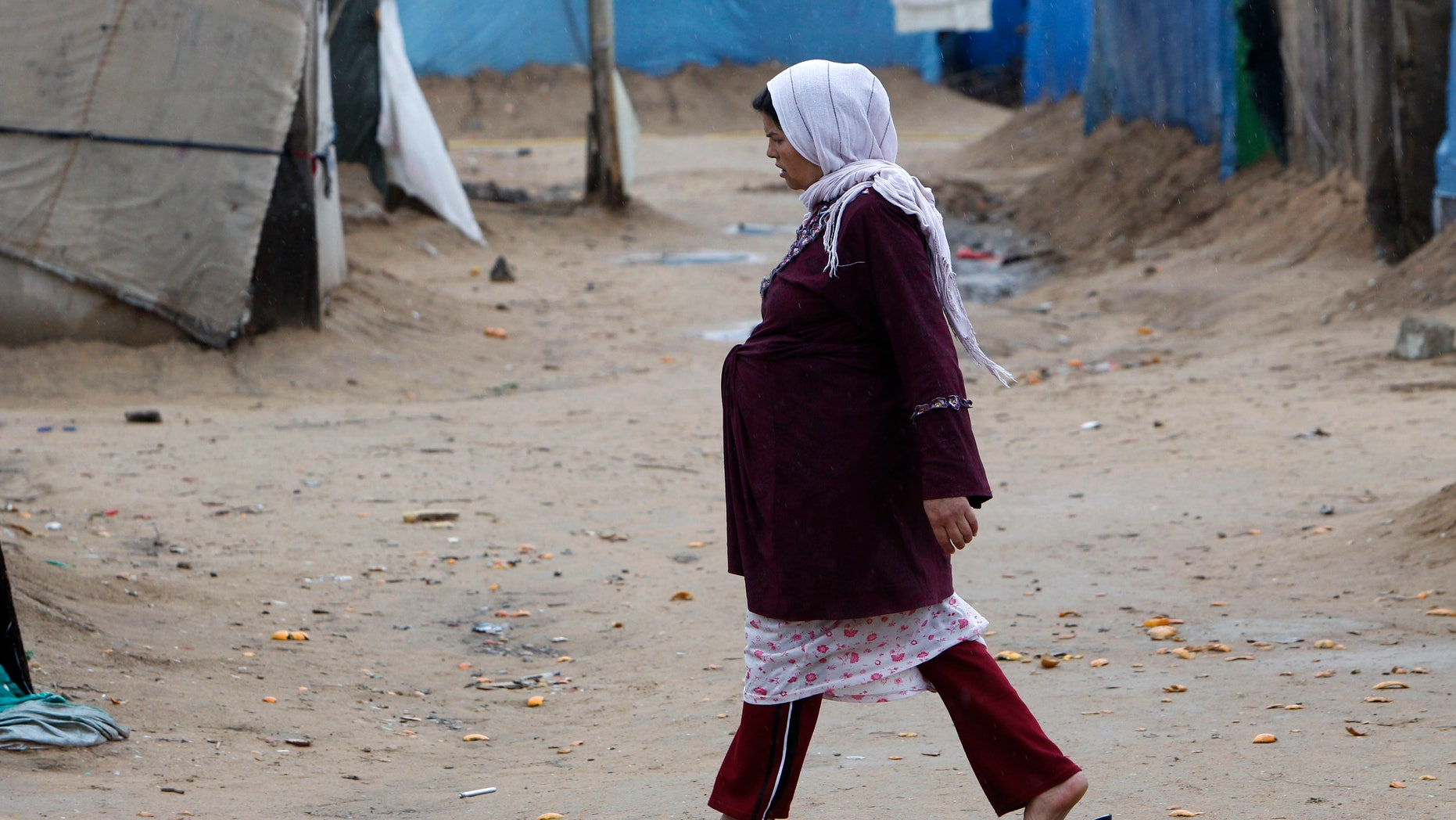A pregnant Syrian woman walks at a refugee camp in the city of Tyre, in southern Lebanon January 31, 2013. REUTERS/Ali Hashisho