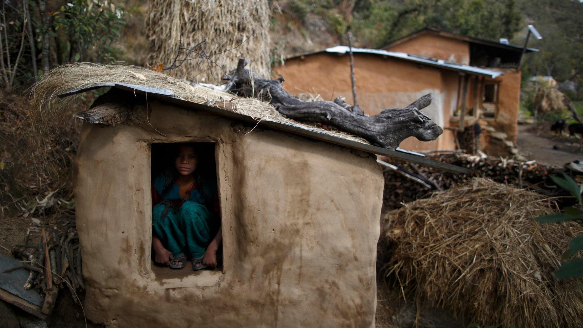 Uttara Saud, 14, sits inside a Chaupadi shed in the hills of Legudsen village in Achham District in western Nepal February 16, 2014