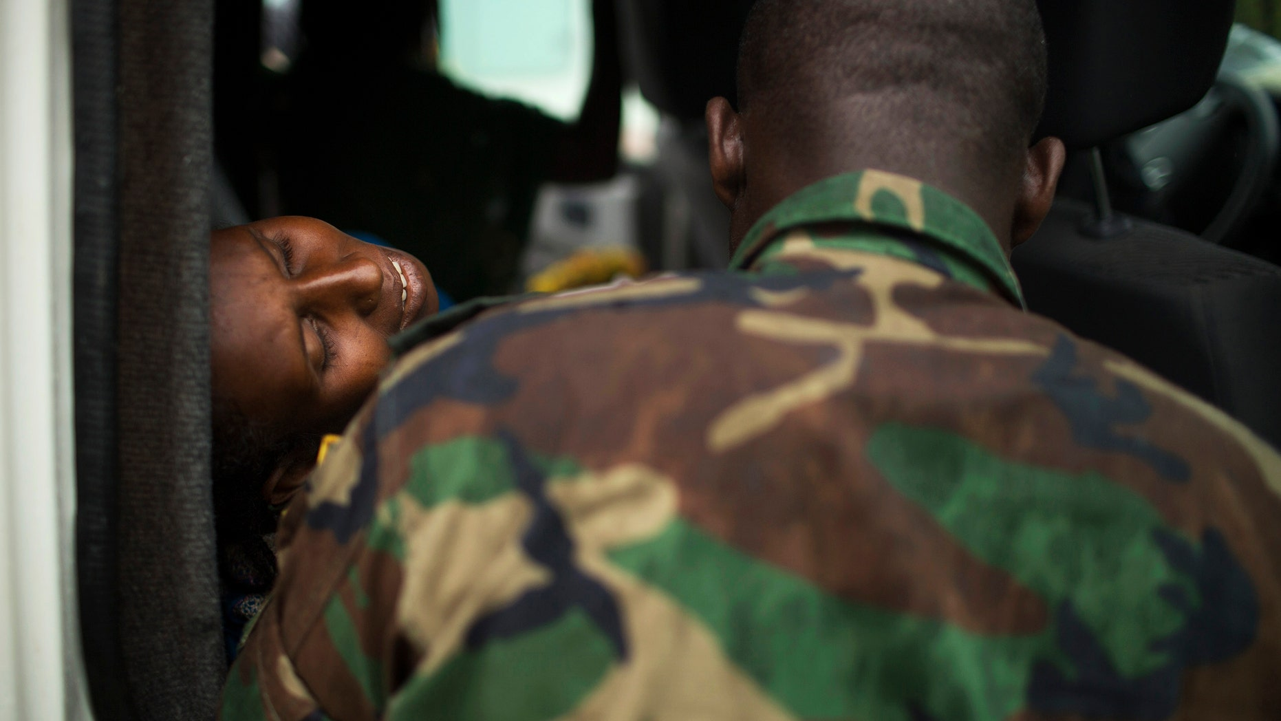 A woman gives birth to twins in the back of a UNICEF vehicle assisted by a medic as she travels in an armed peacekeeping convoy from the African Union operation in CAR (MISCA) escorting about one thousand internally displaced Muslims the northern towns of Kabo and Sido on the border with Chad April 28, 2014. The woman was one of three pregnant wives of a man that are travelling in the convoy. REUTERS/Siegfried Modola (CENTRAL AFRICAN REPUBLIC - Tags: POLITICS CIVIL UNREST CONFLICT RELIGION) - RTR3MZOR