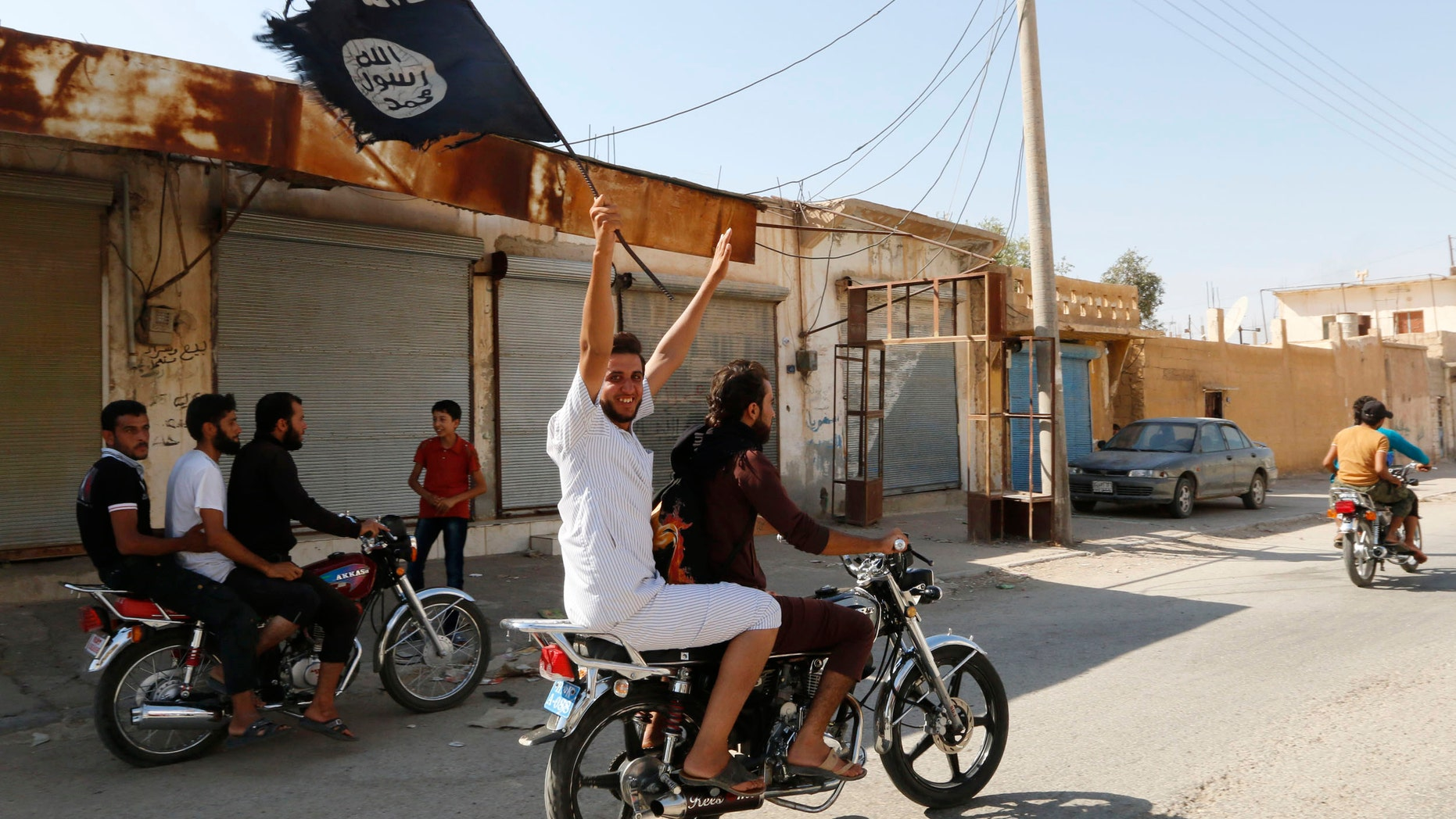 August 24, 2014: A resident of Tabqa city touring the streets on a motorcycle waves an Islamist flag in celebration after Islamic State militants took over Tabqa air base, in nearby Raqqa city. (Reuetrs)