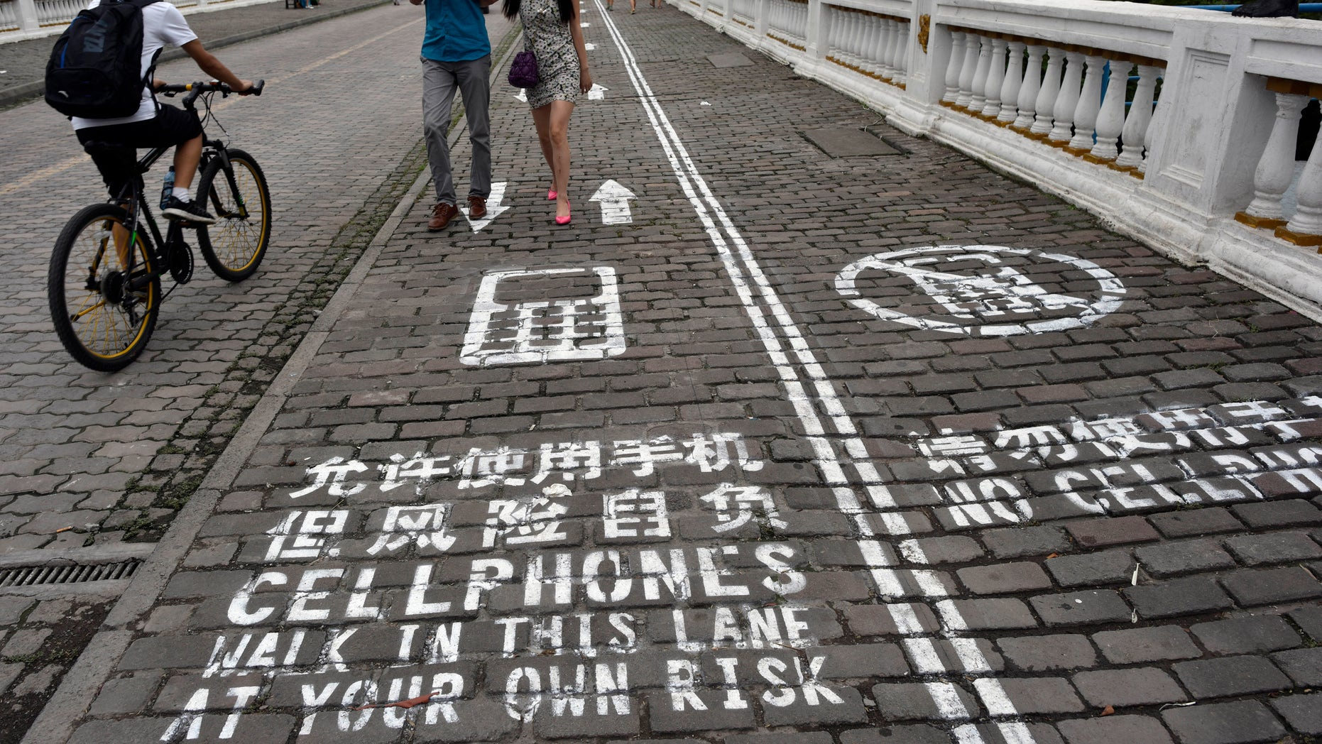 "A man rides his bicycle as people walk on the ""first mobile phone sidewalk in China"", which was recently installed at a tourism area in Chongqing municipality, September 13, 2014. The mobile phone sidewalk in Chongqing was divided into two sides -- one was written with ""Cellphones walk in this lane at your own risk"" while the other with ""No cellphones"", as an attempt to reduce pedestrian incidents, local media reported. Picture taken September 13, 2014. REUTERS/China Daily"