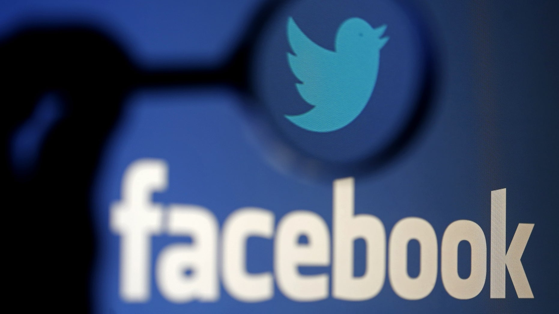 A logo of Twitter is pictured next to the logo of Facebook in this photo illustration.