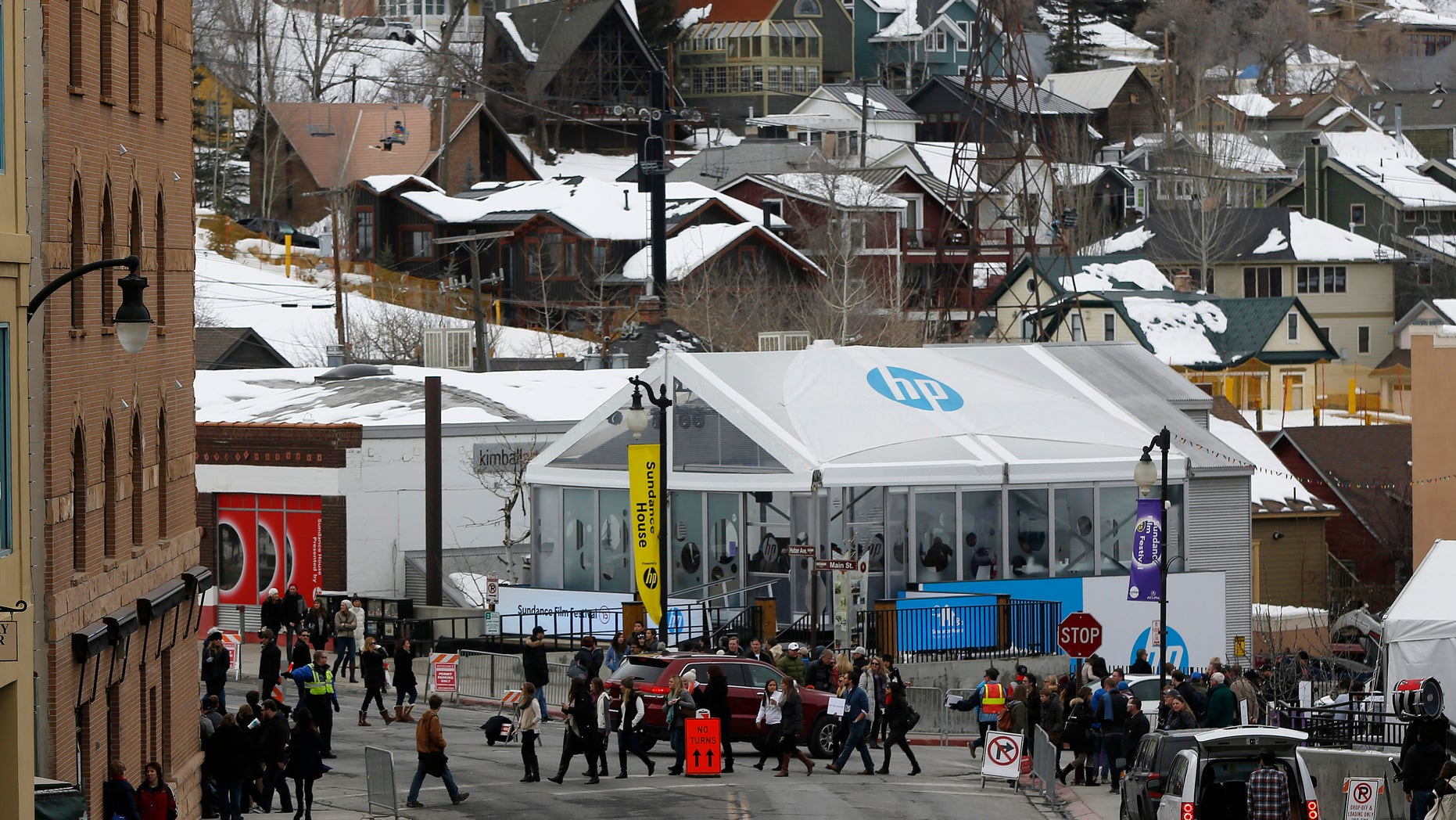 Pedestrians cross the street near skiers on a lift during Sundance Film Festival in Park City, Utah, January 24, 2015.