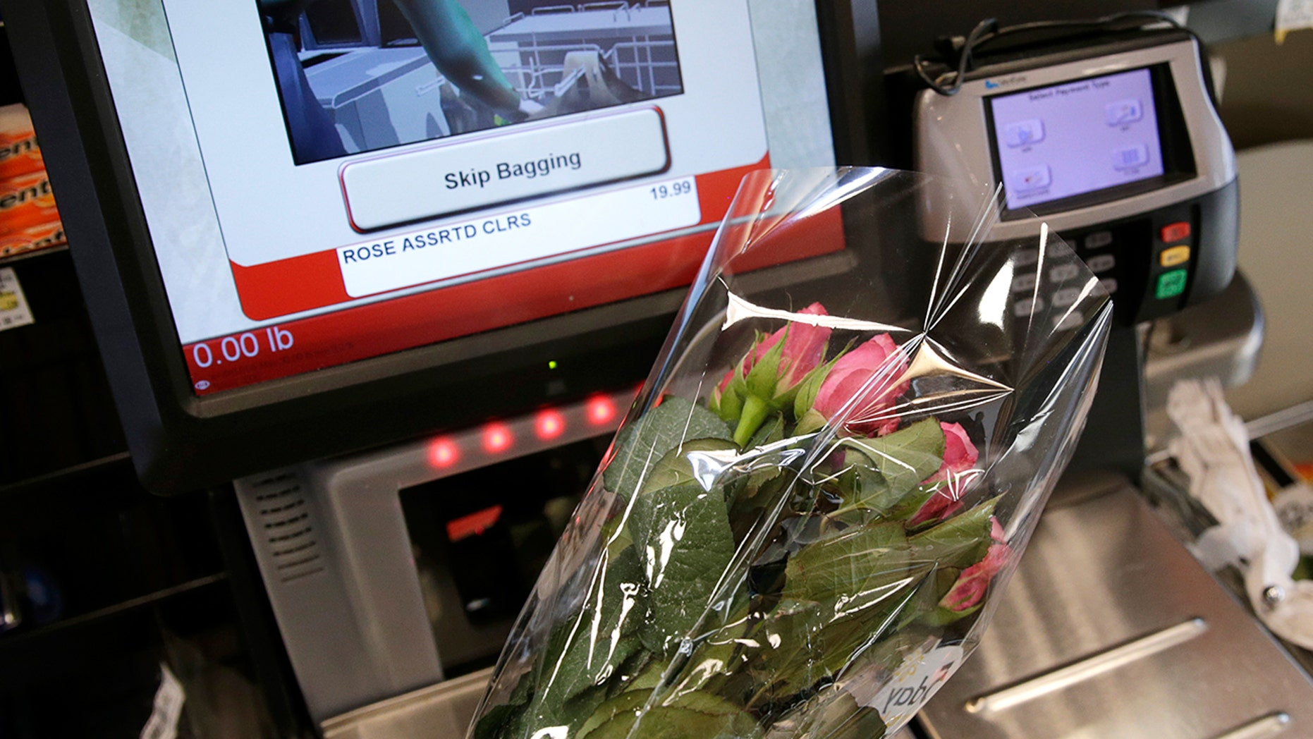 Flowers are scanned at a self check out station.