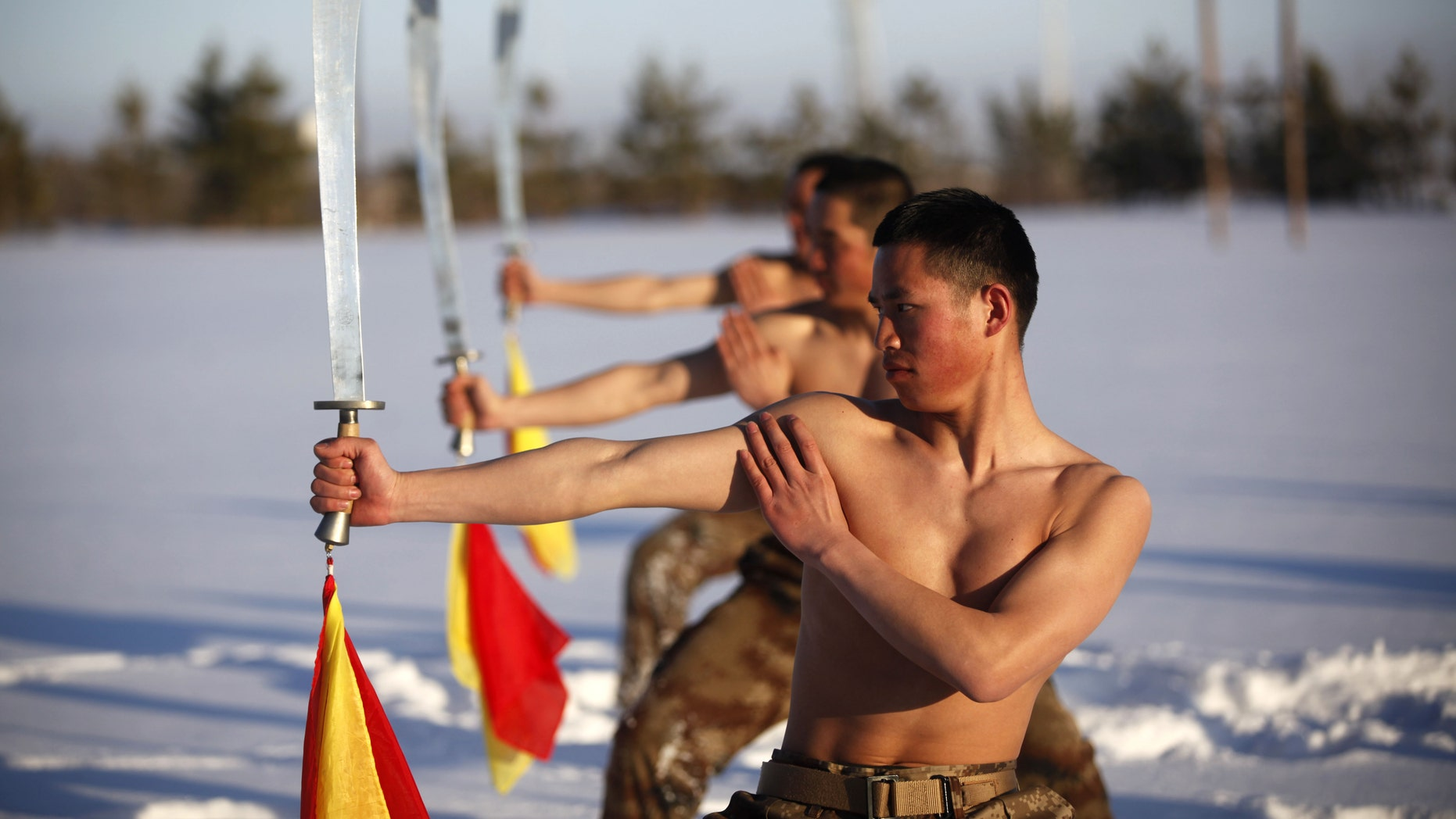 File photo: Soldiers of China's People's Liberation Army (PLA) practice with swords as they take part in a winter training at China's border with Russia in Heihe, Heilongjiang province, February 27, 2015.