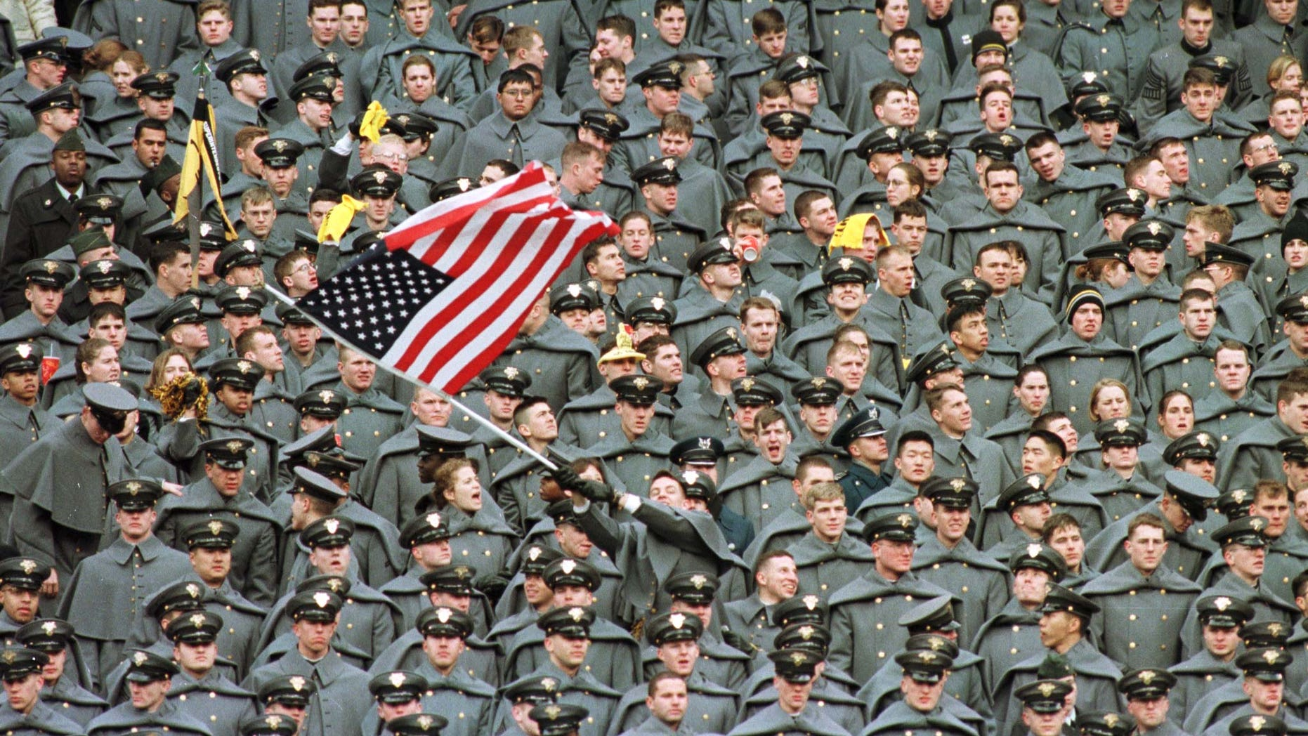 A lone West Point Cadet waves the American flag amid a sea of fellow Cadets as they watch Navy take a commanding lead in the first half of the Army-Navy game, December 6 1997 at Giants Stadium in East Rutherford.