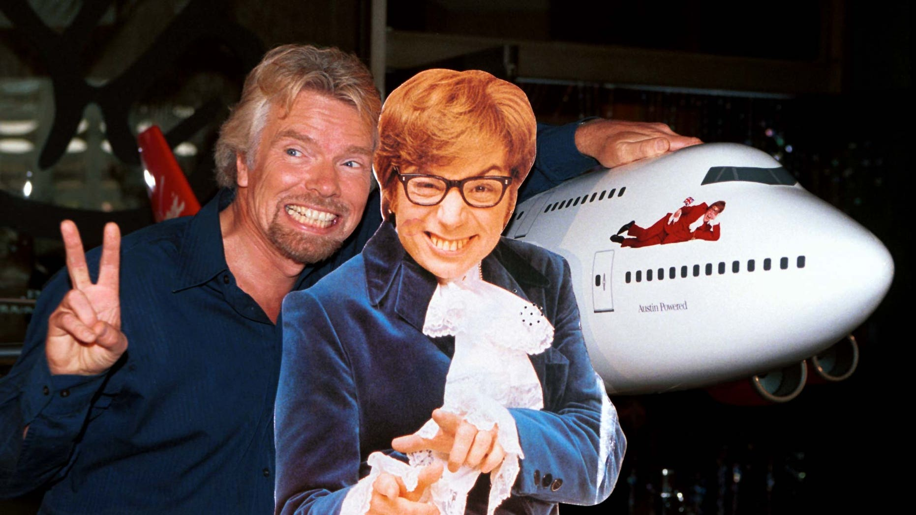 "Virgin Atlantic Airways CEO Richard Branson (L) poses with a cut-out of actor Mike Myers, as Austin Powers, after christening ceremonies of Virgin Shaglantic Flight double-O-Seven at Los Angeles International Airport, May 10. The unveiling of the renamed and redecorated airliner signaled the start of a dynamic global air travel marketing blitz in the partnership with the release of the New Line Cinema movie ""Austin Powers: The Spy Who Shagged Me""."