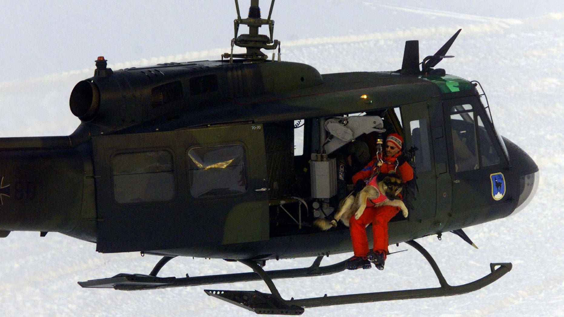 German mountain rescue worker Stefan Bonleitner and his avalanche dog Gina prepares to winch out of a helicopter during a press demonstration of German mountain rescue workers in the Alps near Garmisch-Partenkirchen, January 20, 1999.
