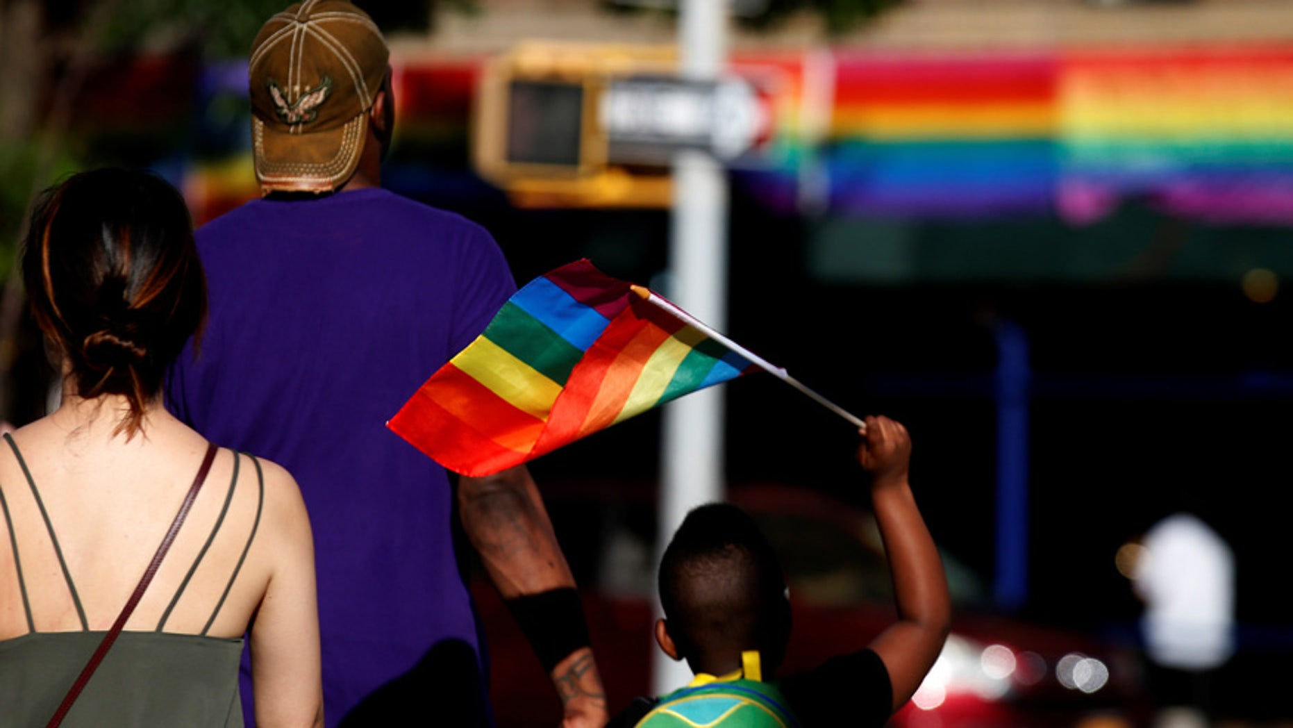 A boy carries a rainbow flag near The Stonewall Inn, on the eve of the LGBT Pride March, in the Greenwich Village section of New York City, U.S. June 24, 2017. REUTERS/Brendan McDermid - RTS18ID1